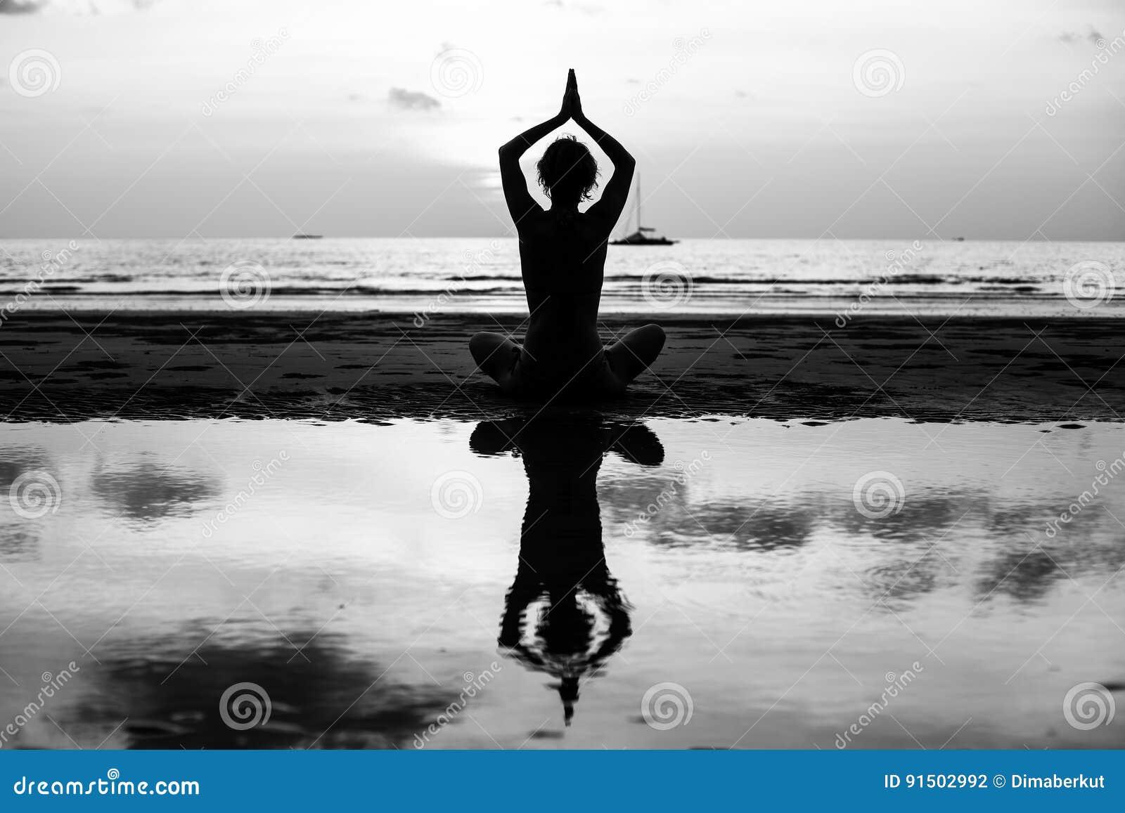 Silueta blanco y negro de la mujer de la yoga que medita en la orilla de mar Relájese