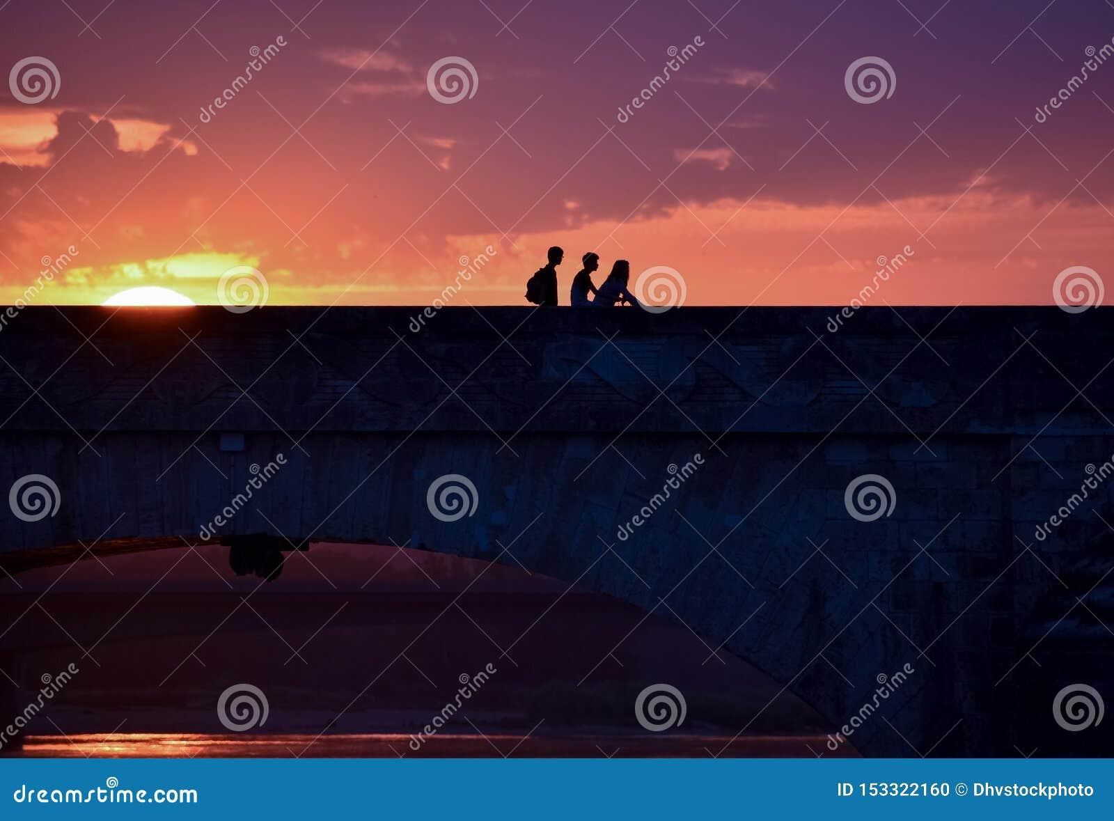 Silueta de amigos jovenes en una puesta del sol colorida al volver el hogar, cruzando un puente
