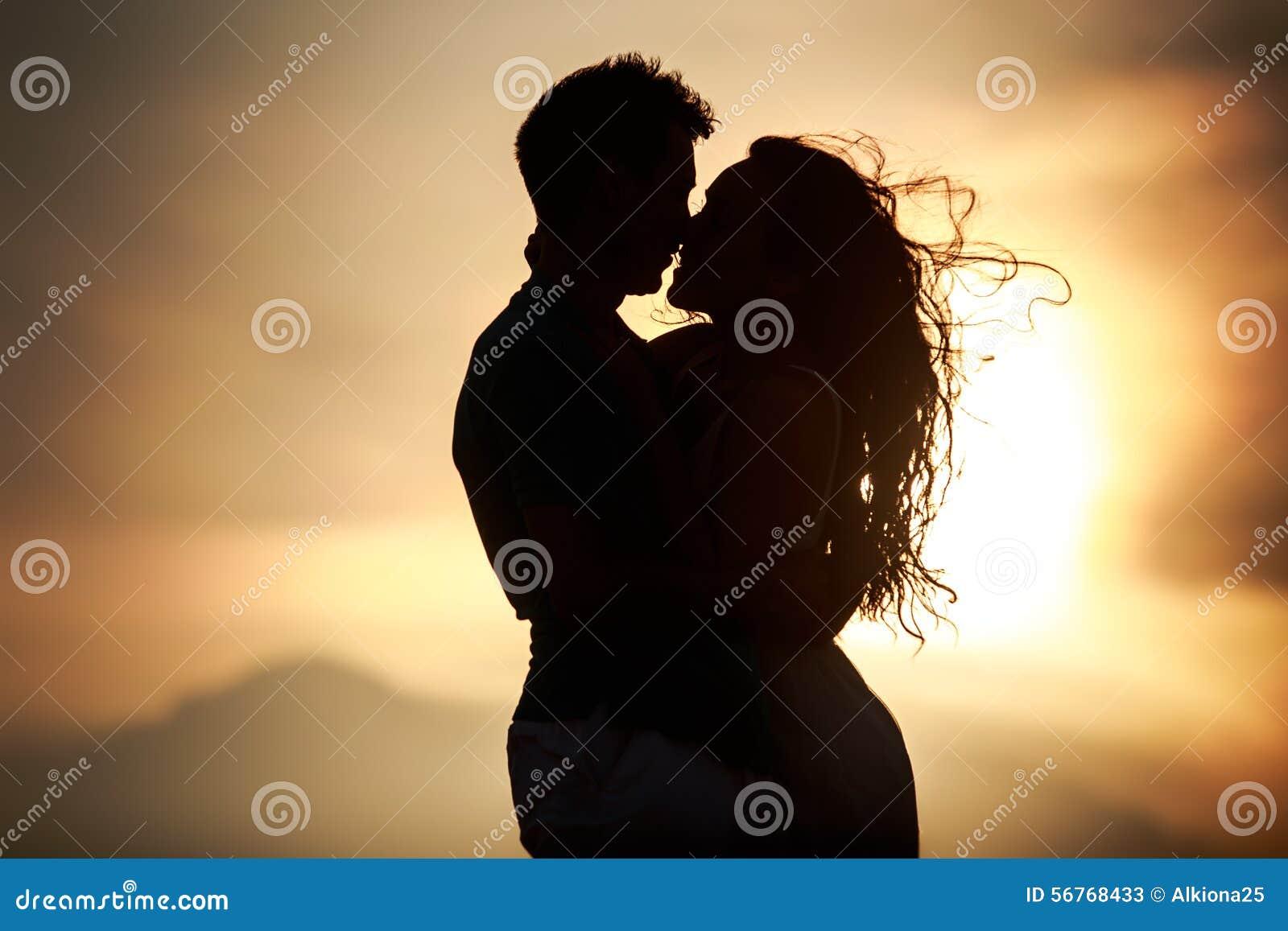 Silueta de besar el individuo y a la muchacha en el amanecer