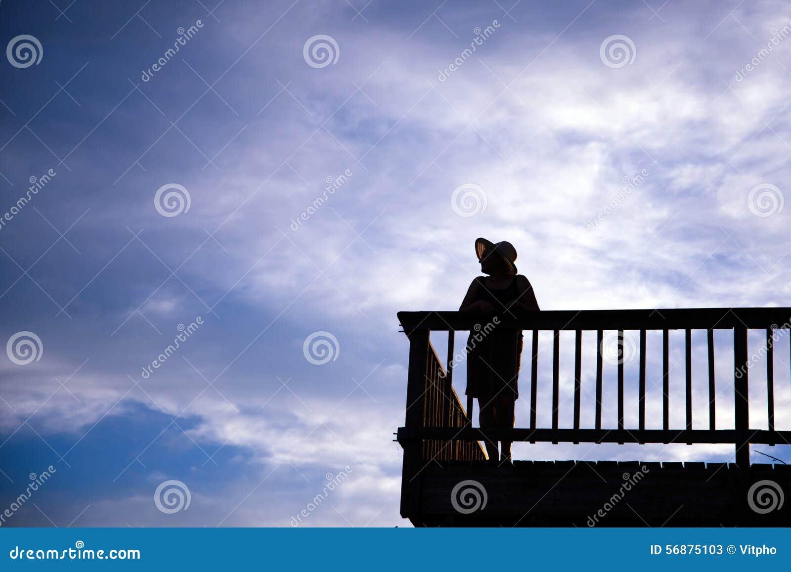 Silueta de la forma impresionante de la mujer en el sombrero que se coloca en balcón encendido