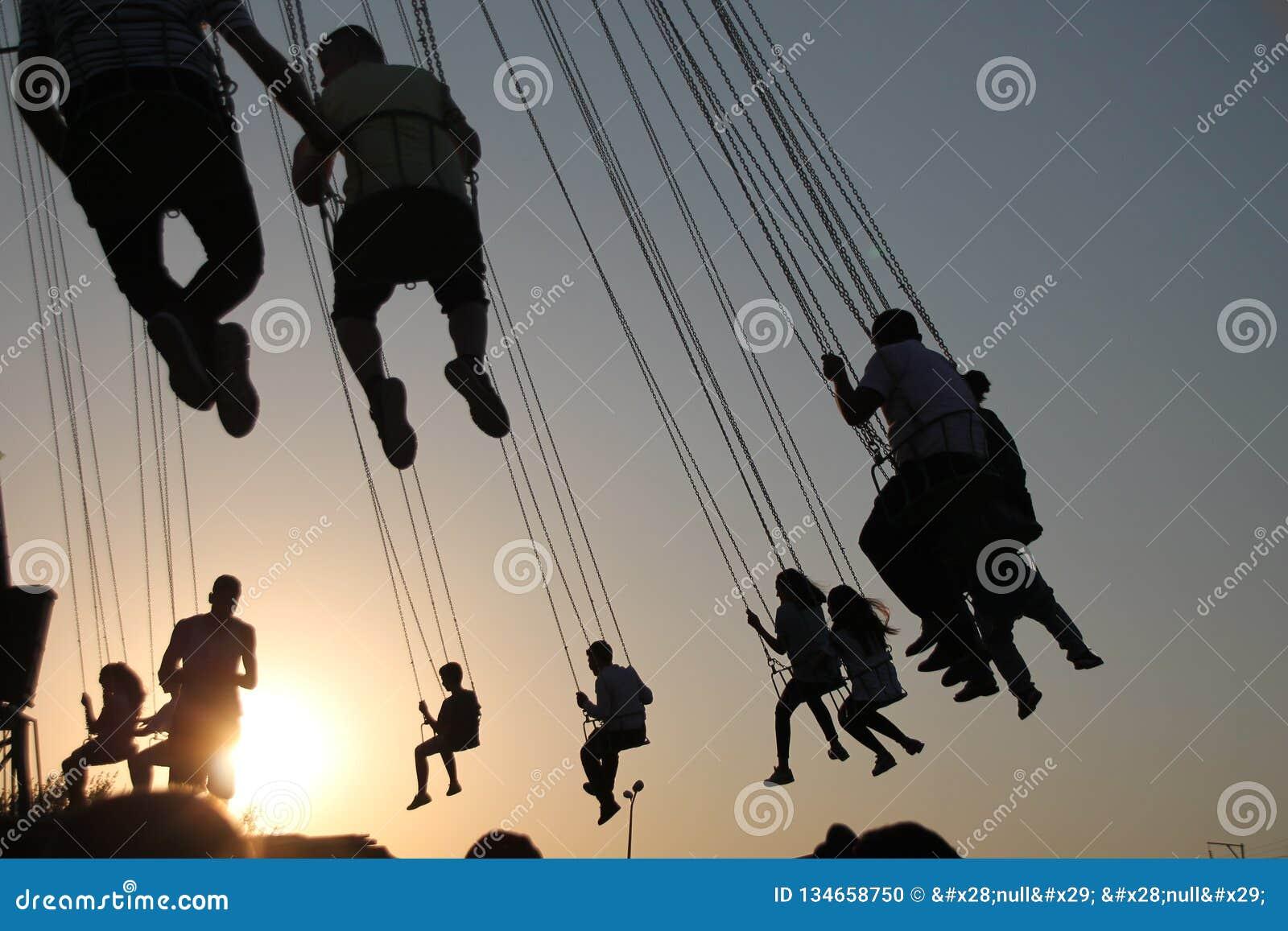 Silueta de la gente joven en la noria y el carrusel de balanceo en el movimiento de parada en fondo de la puesta del sol