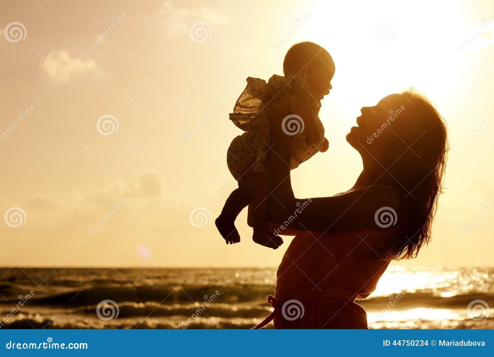 Silueta De La Madre Y Del Bebé En La Puesta Del Sol Foto