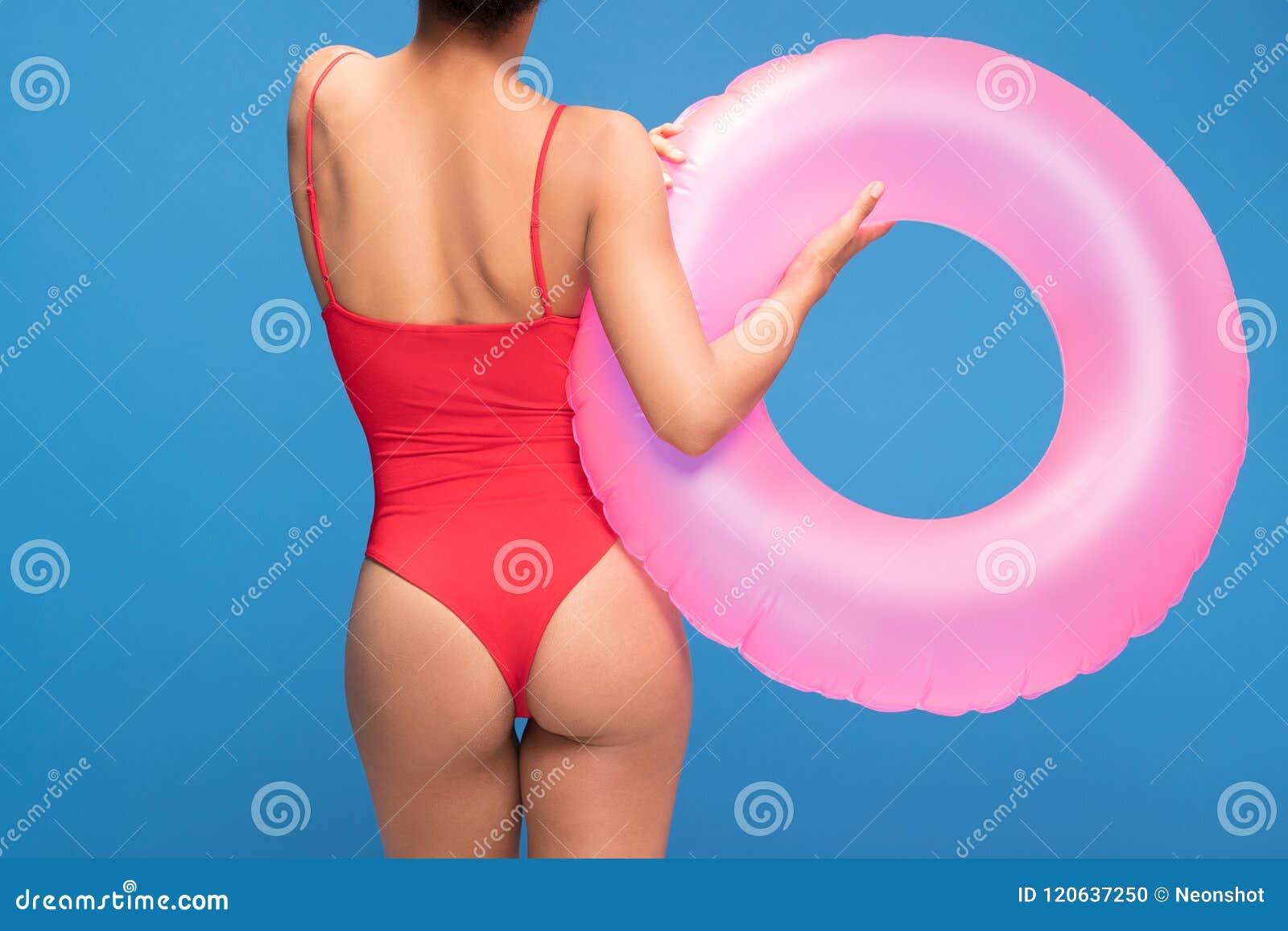 Silueta de la mujer atractiva del ajuste en traje de baño rojo