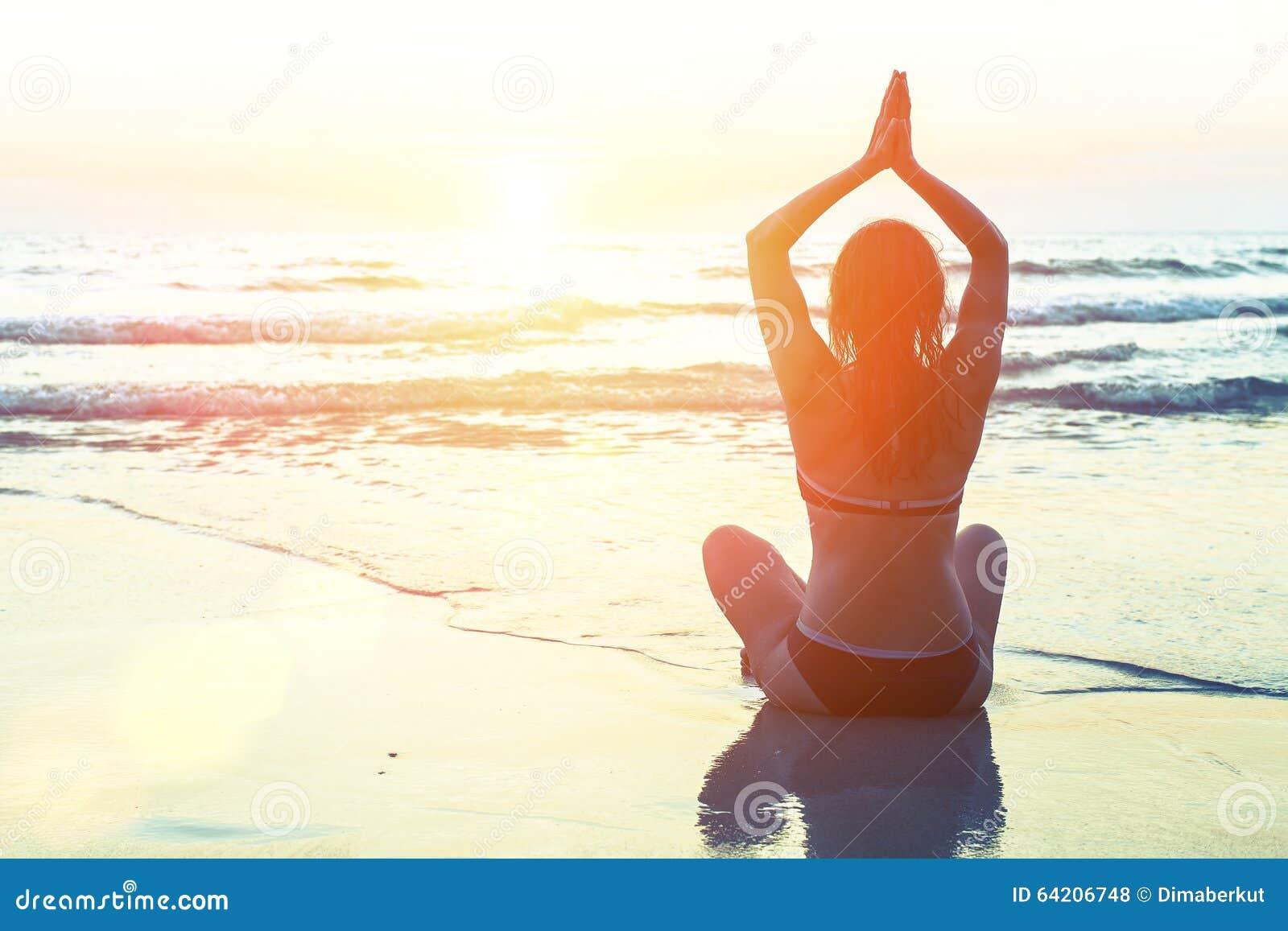 Silueta de la mujer de la yoga de la meditación en el fondo del mar y de la puesta del sol asombrosa