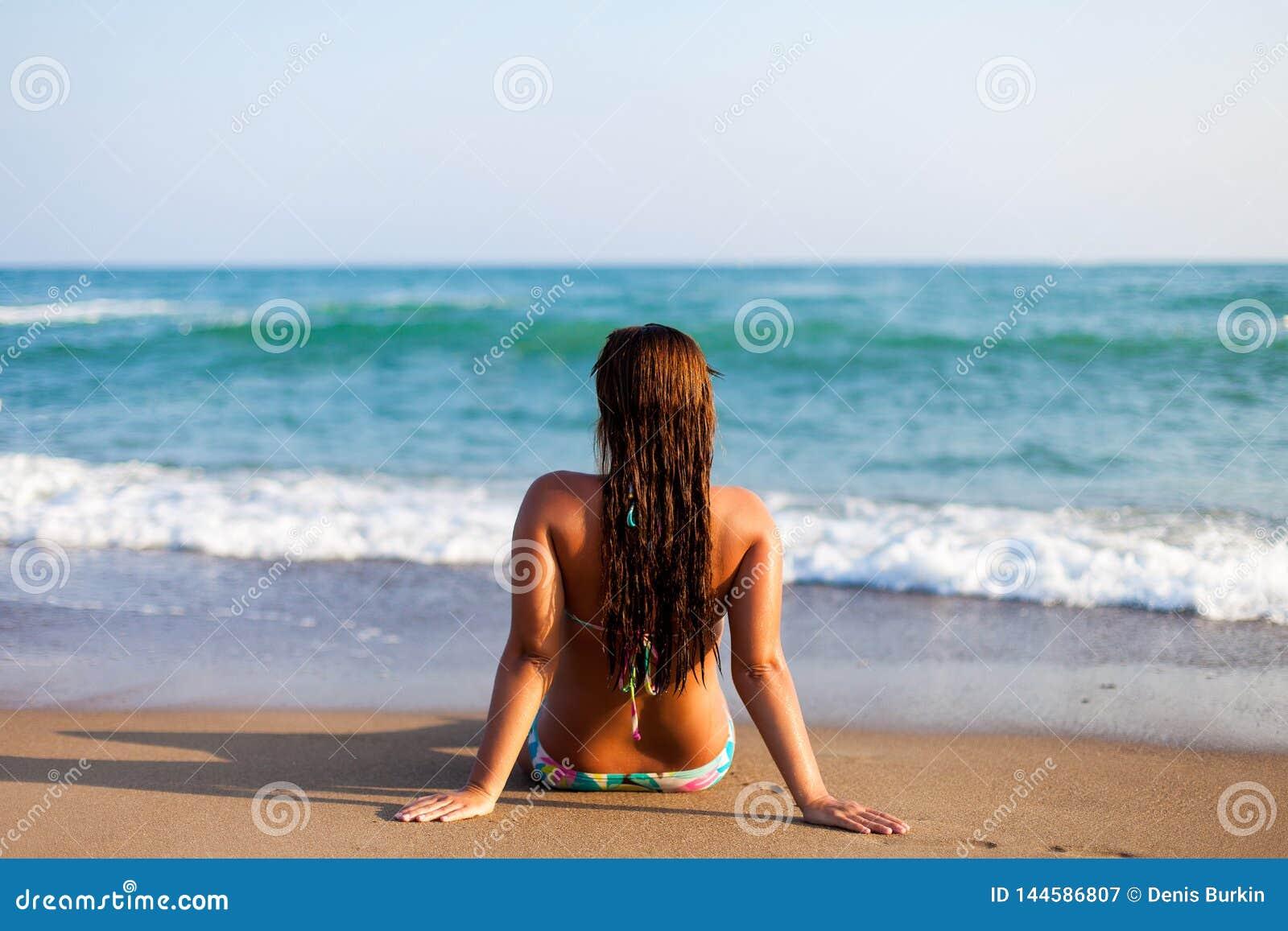 Silueta de la mujer joven en la playa Mujer joven que se sienta delante de la playa Muchacha en el bikini que se relaja en la pla