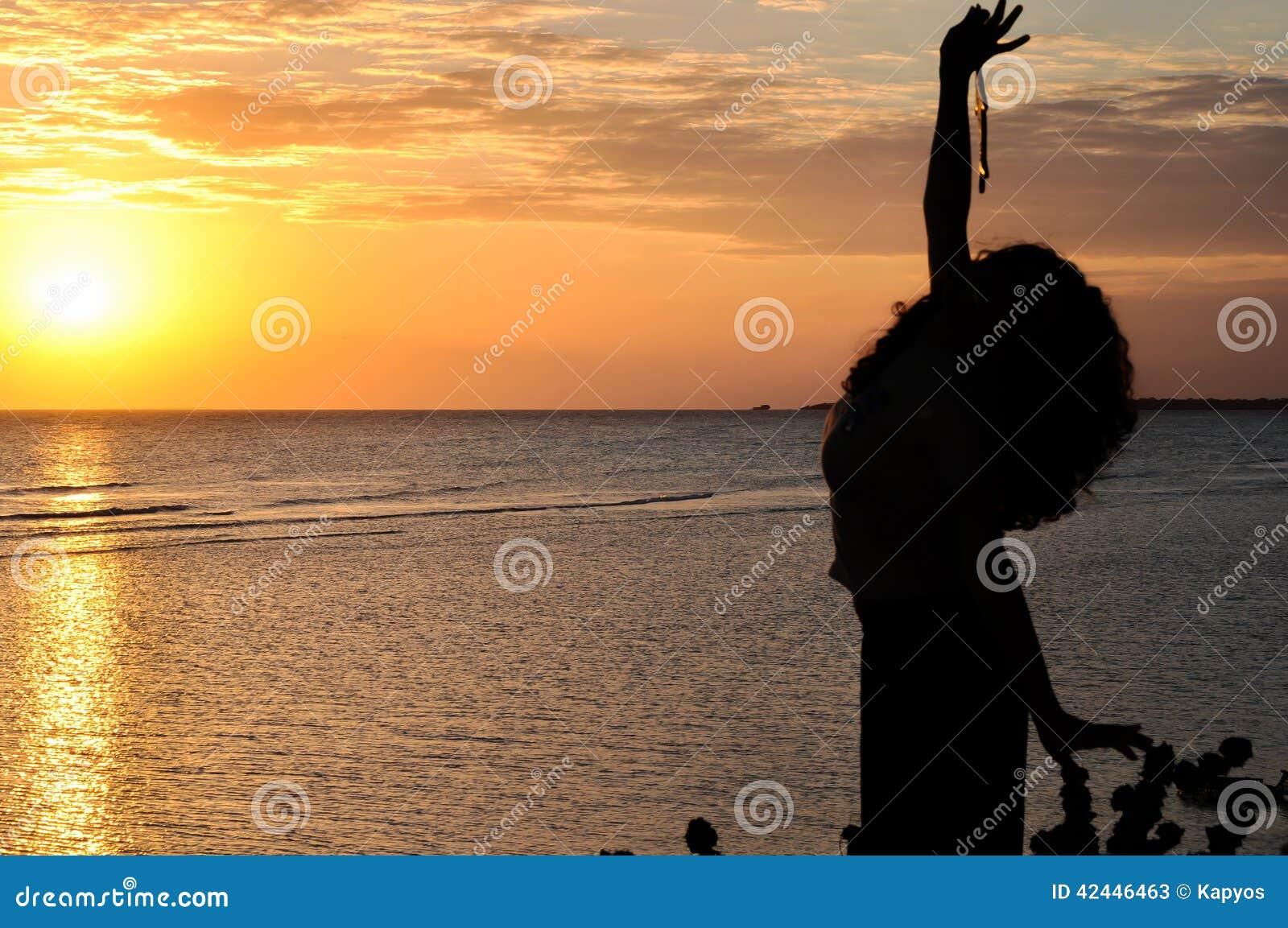 Silueta de la mujer joven que hace una pausa el mar