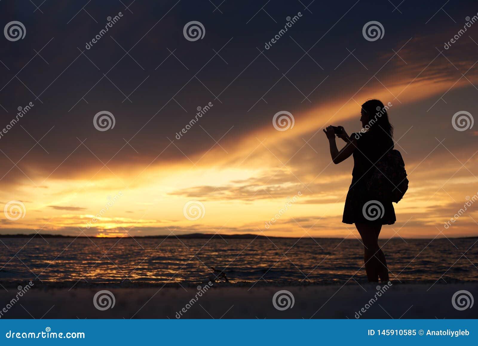 Silueta de la mujer solamente en el borde del agua, disfrutando de paisaje marino hermoso en la puesta del sol