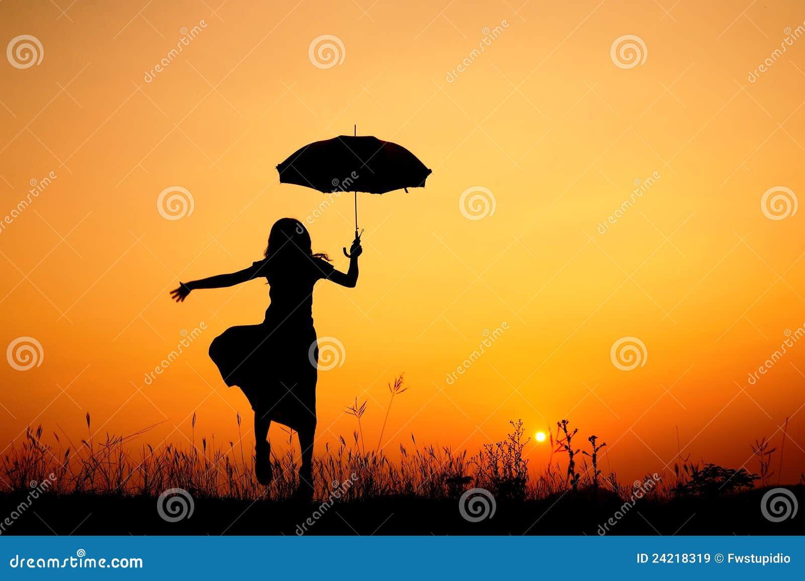 Silueta De La Mujer Y De La Puesta Del Sol Del Paraguas