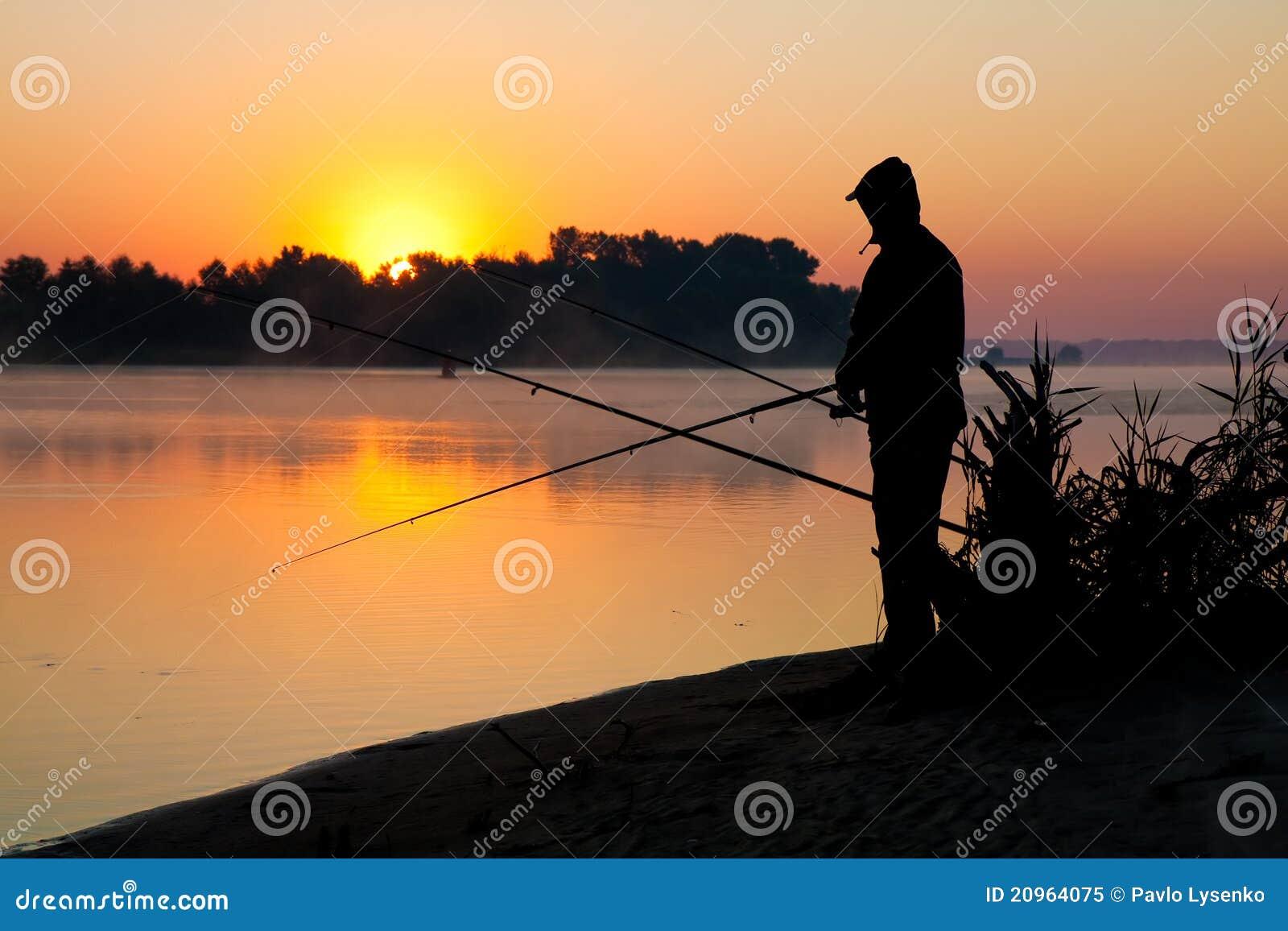 Silueta de la pesca del hombre en una puesta del sol