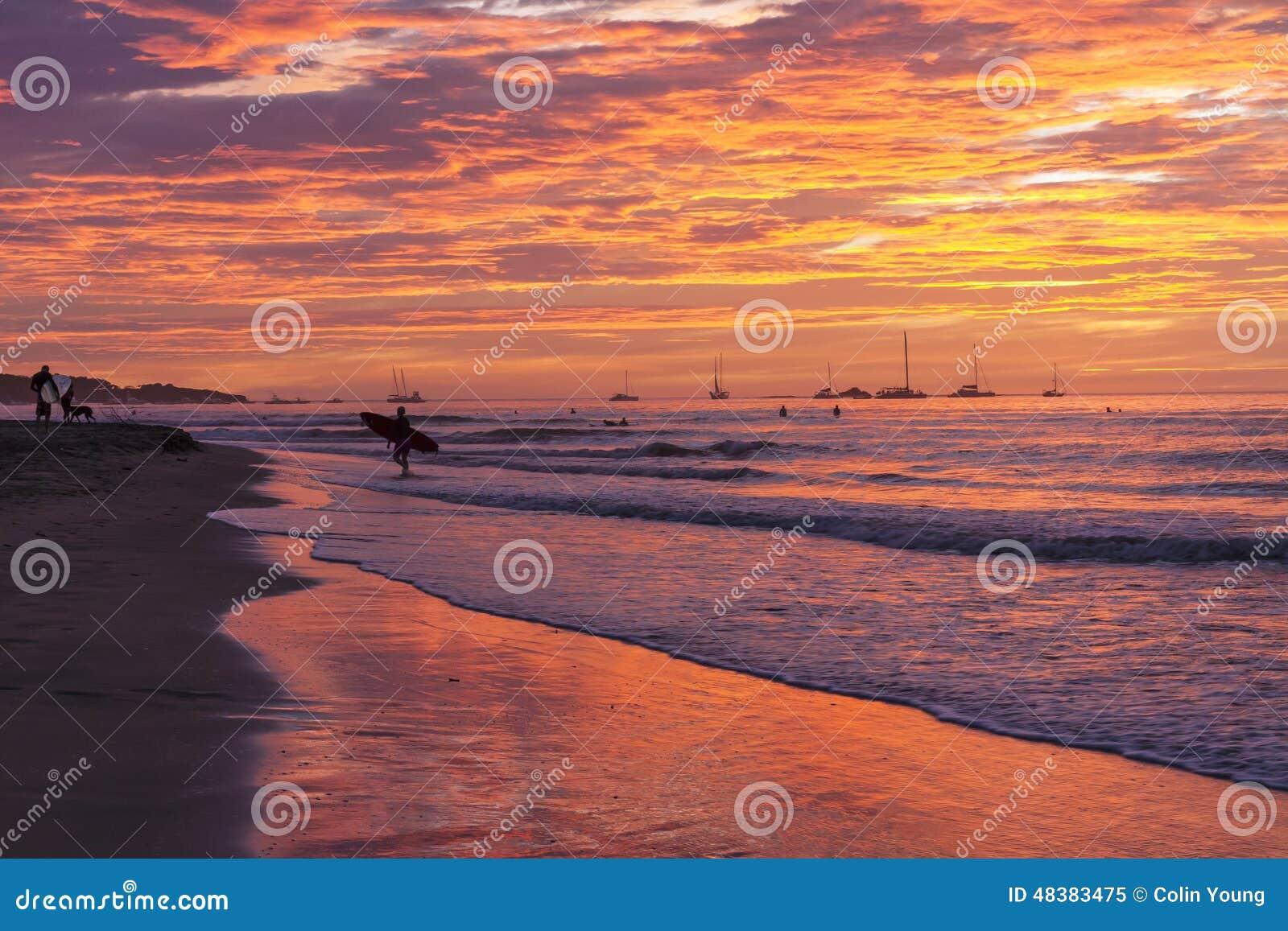 Silueta de la puesta del sol de la persona que practica surf en orilla