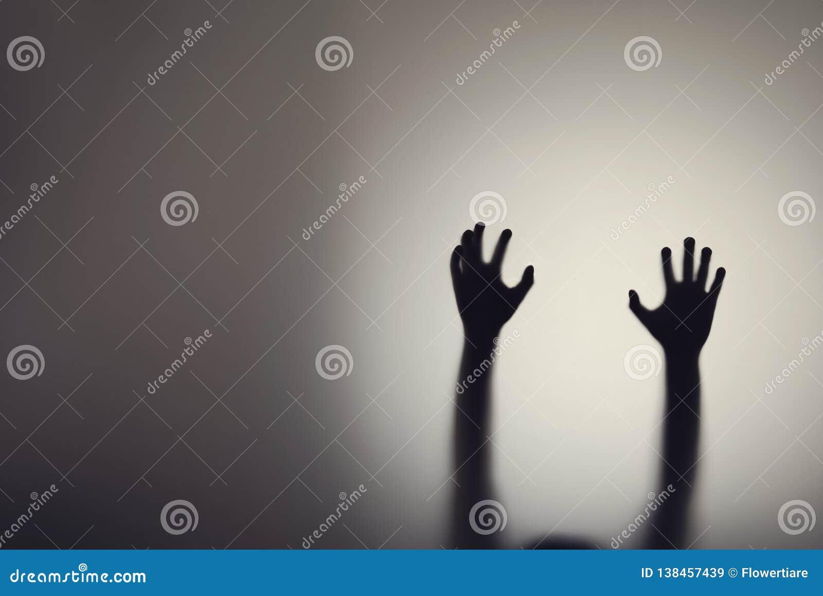 Silueta de las manos de la mujer detrás de la puerta de cristal Concepto de depresión, miedo, ataques de pánico