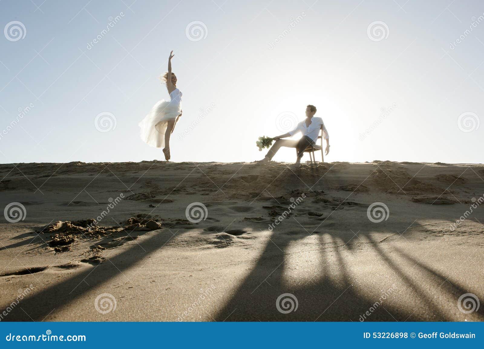 Silueta de los pares hermosos jovenes que cuelgan hacia fuera junto en la playa