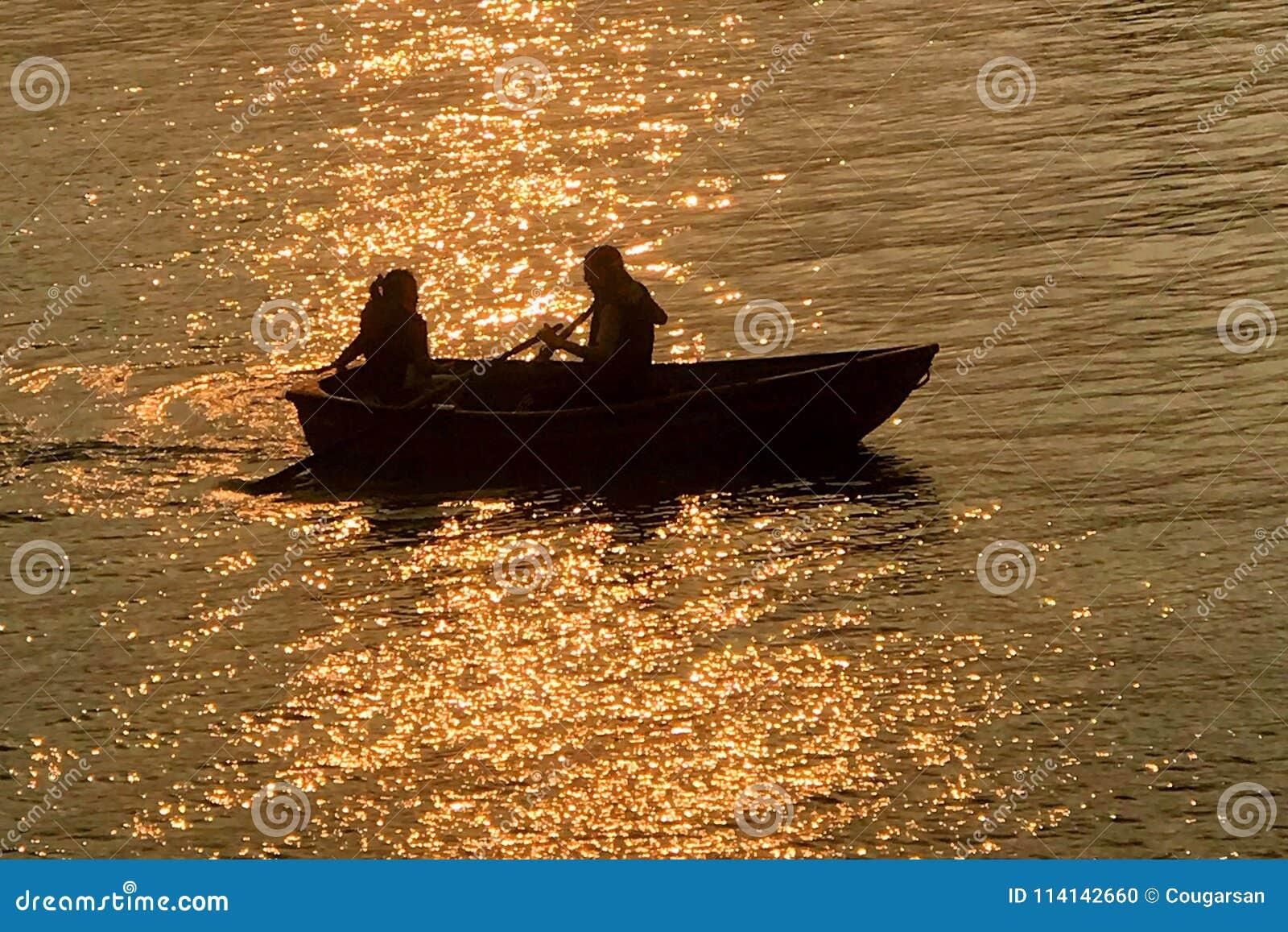 Silueta de los pares de la datación, barco recreativo en el lago en la puesta del sol