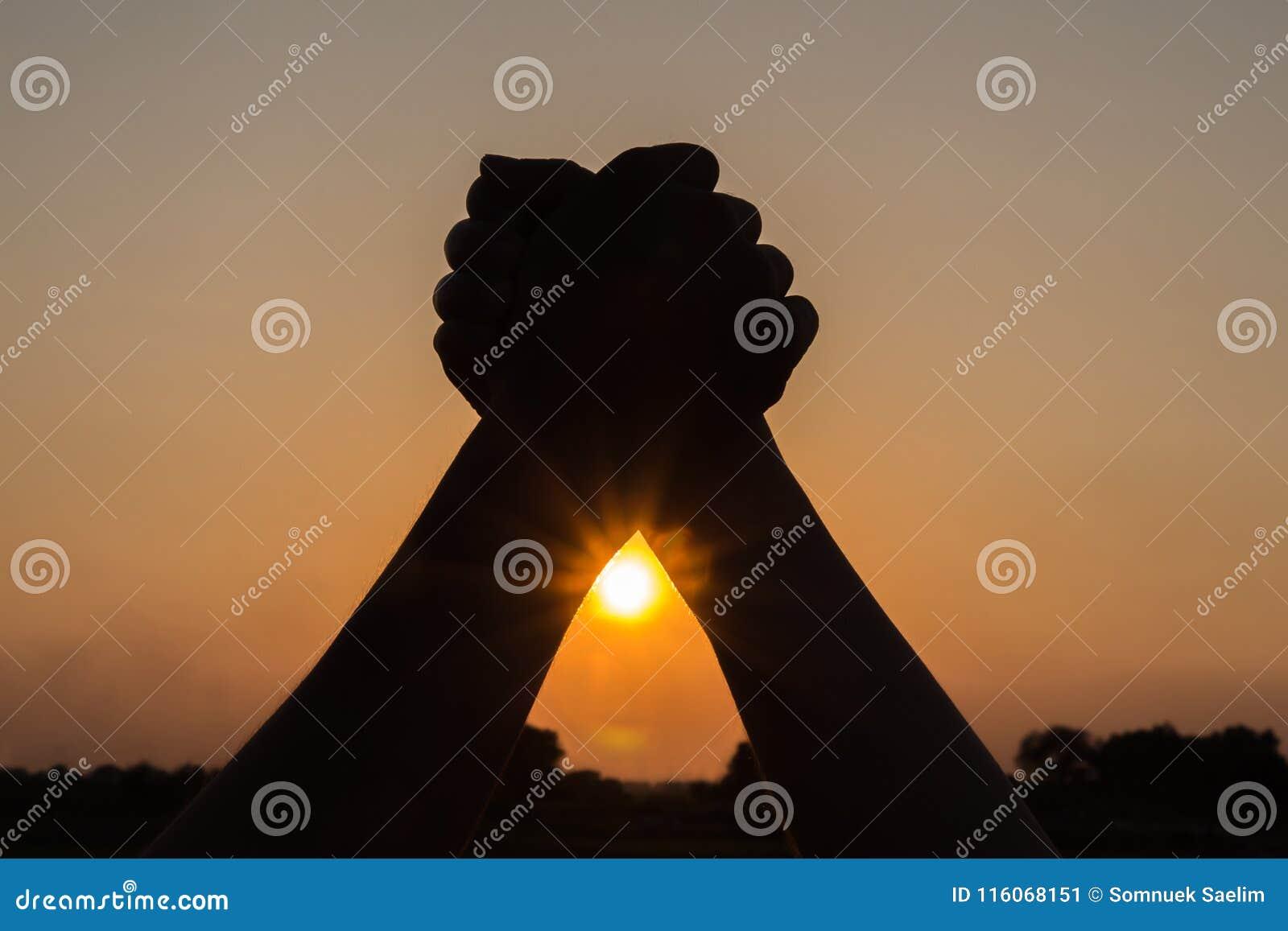 Silueta de los pares que llevan a cabo las manos para arriba que celebran beauti de la victoria