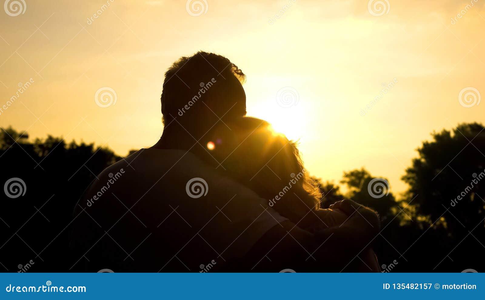 Silueta de los viejos pares de abrazo, puesta del sol de observación junto, edad avanzada segura