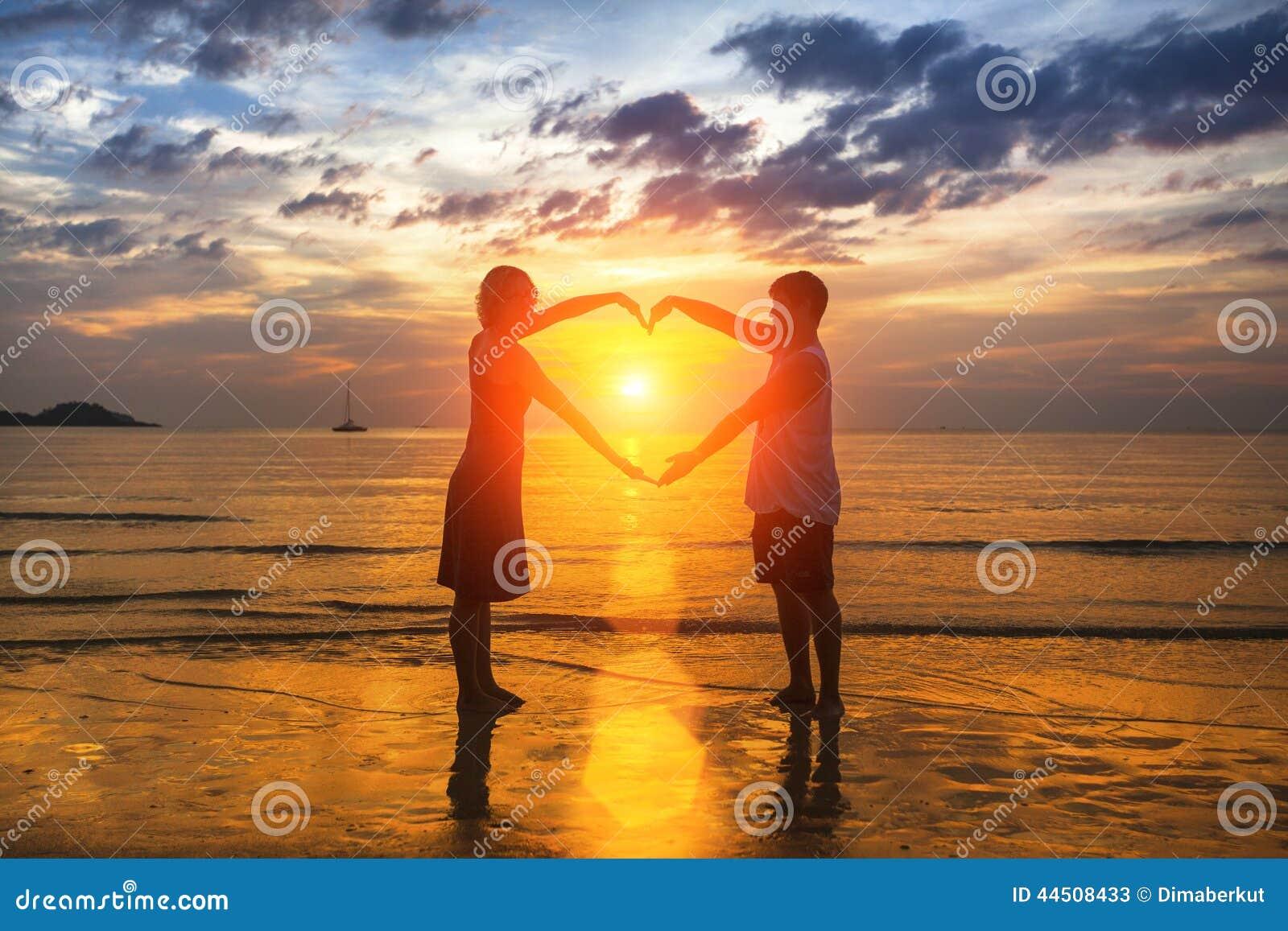 Silueta de pares cariñosos durante una puesta del sol asombrosa, llevando a cabo las manos en forma del corazón Amor