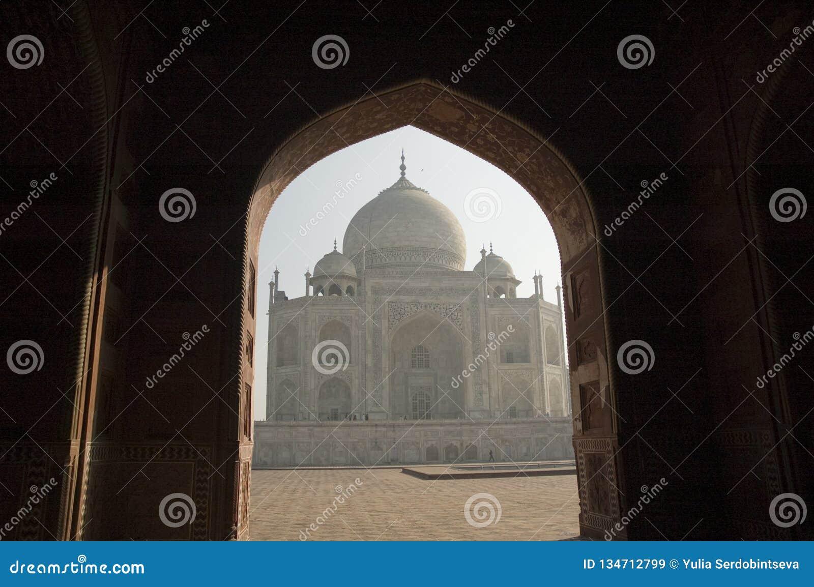 Silueta de Taj Mahal a través de una arcada agra La India