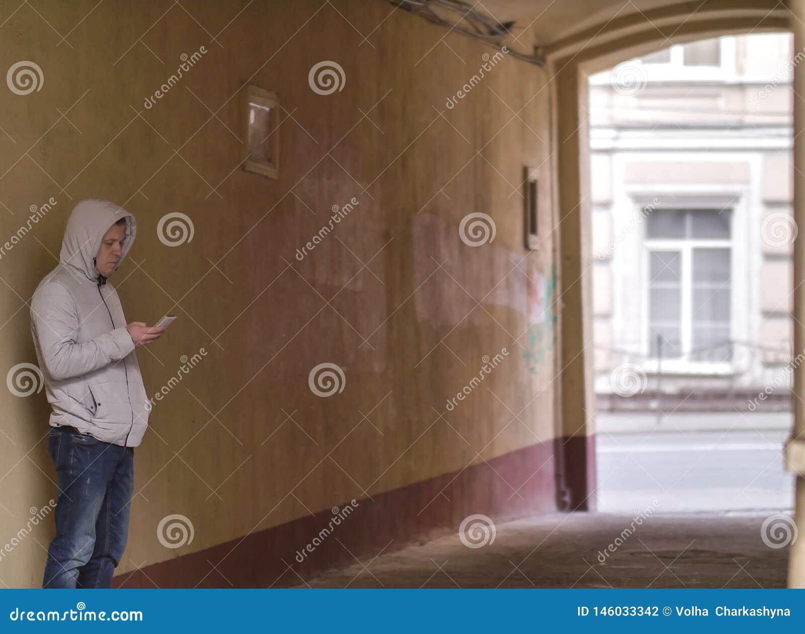 Silueta de un hombre en la capilla con la situación del teléfono en el arco del patio