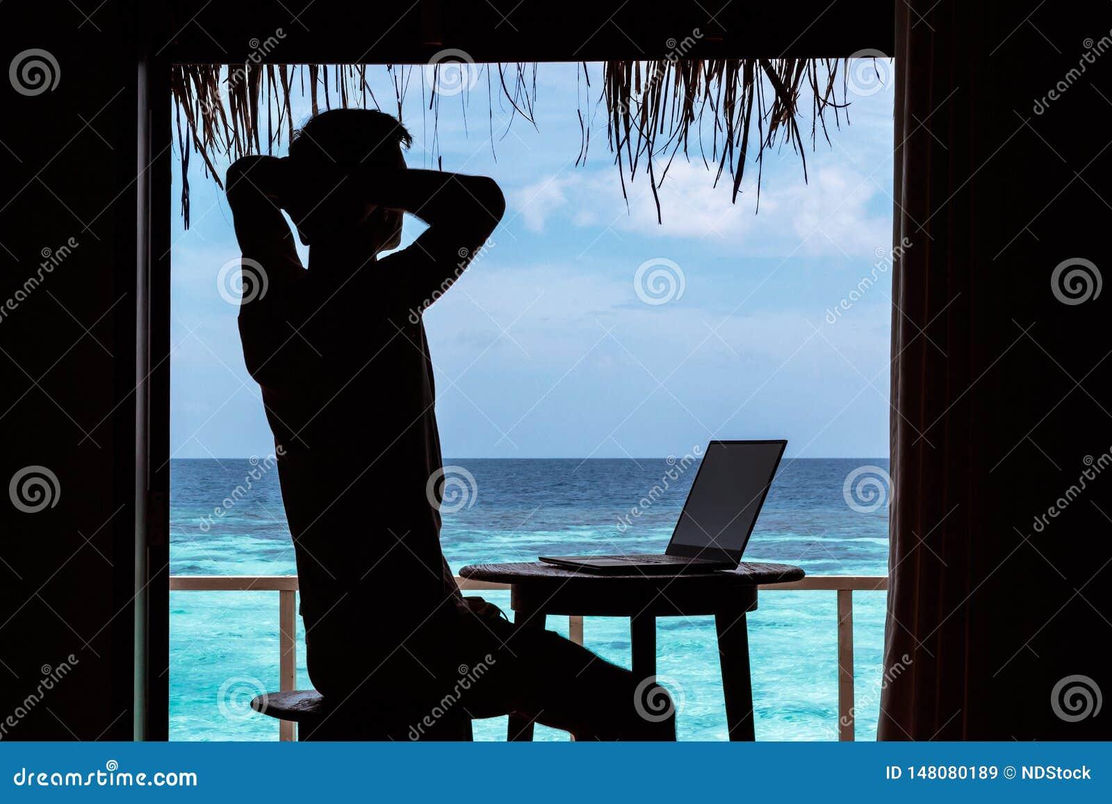 Silueta de un hombre joven que se relaja mientras que trabaja con un ordenador en una tabla Agua tropical azul clara como fondo