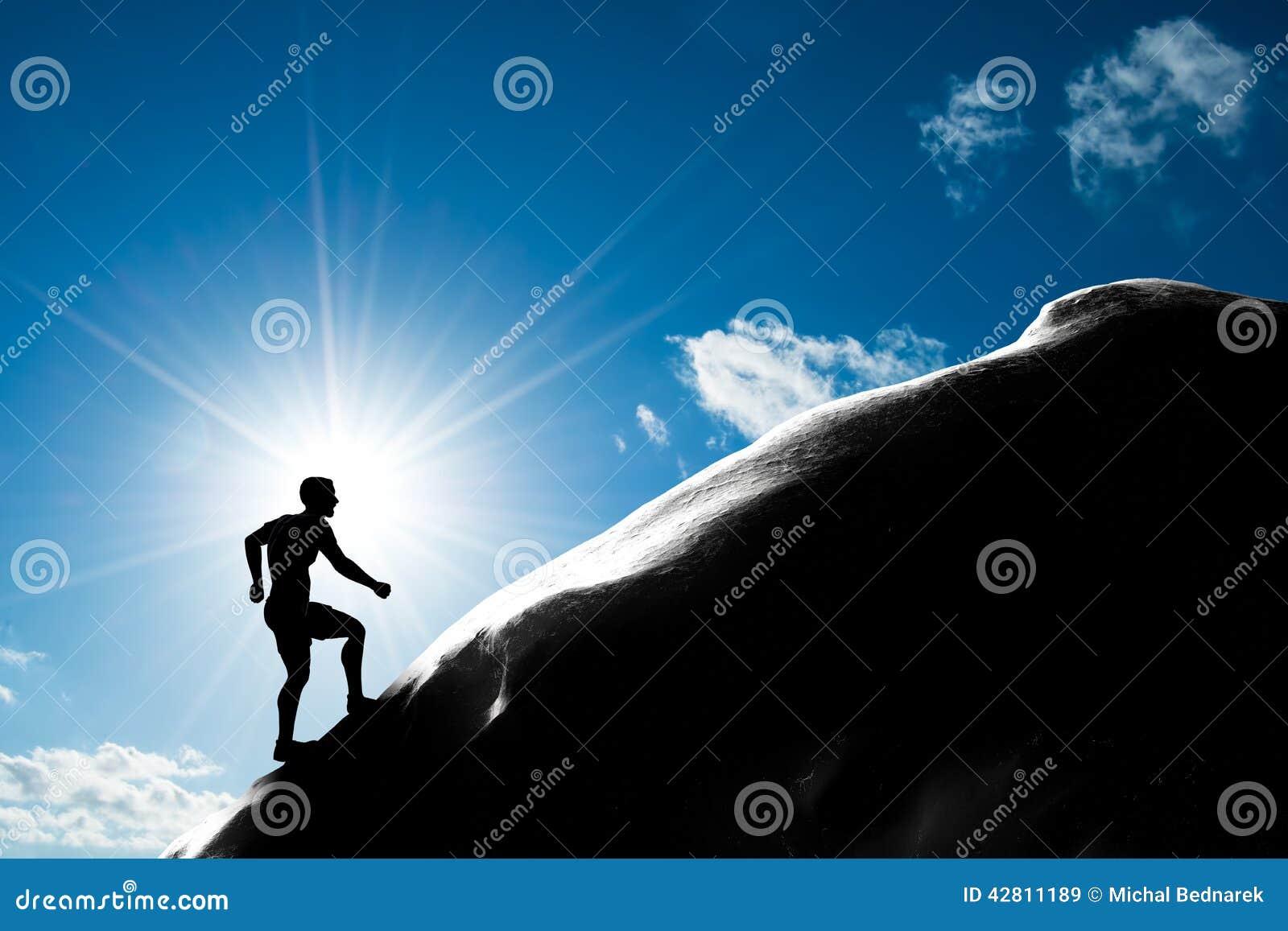 Silueta de un hombre que funciona con para arriba la colina al pico de la montaña
