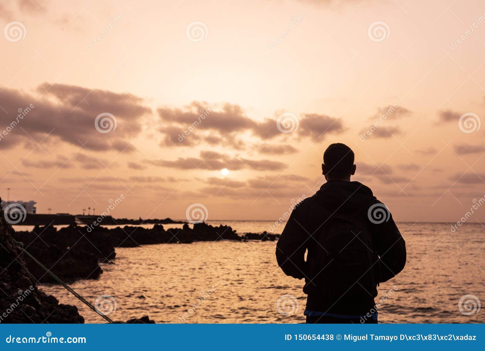 Silueta de un muchacho joven en la puesta del sol, mirando el sol en Lanzarote, islas Canarias