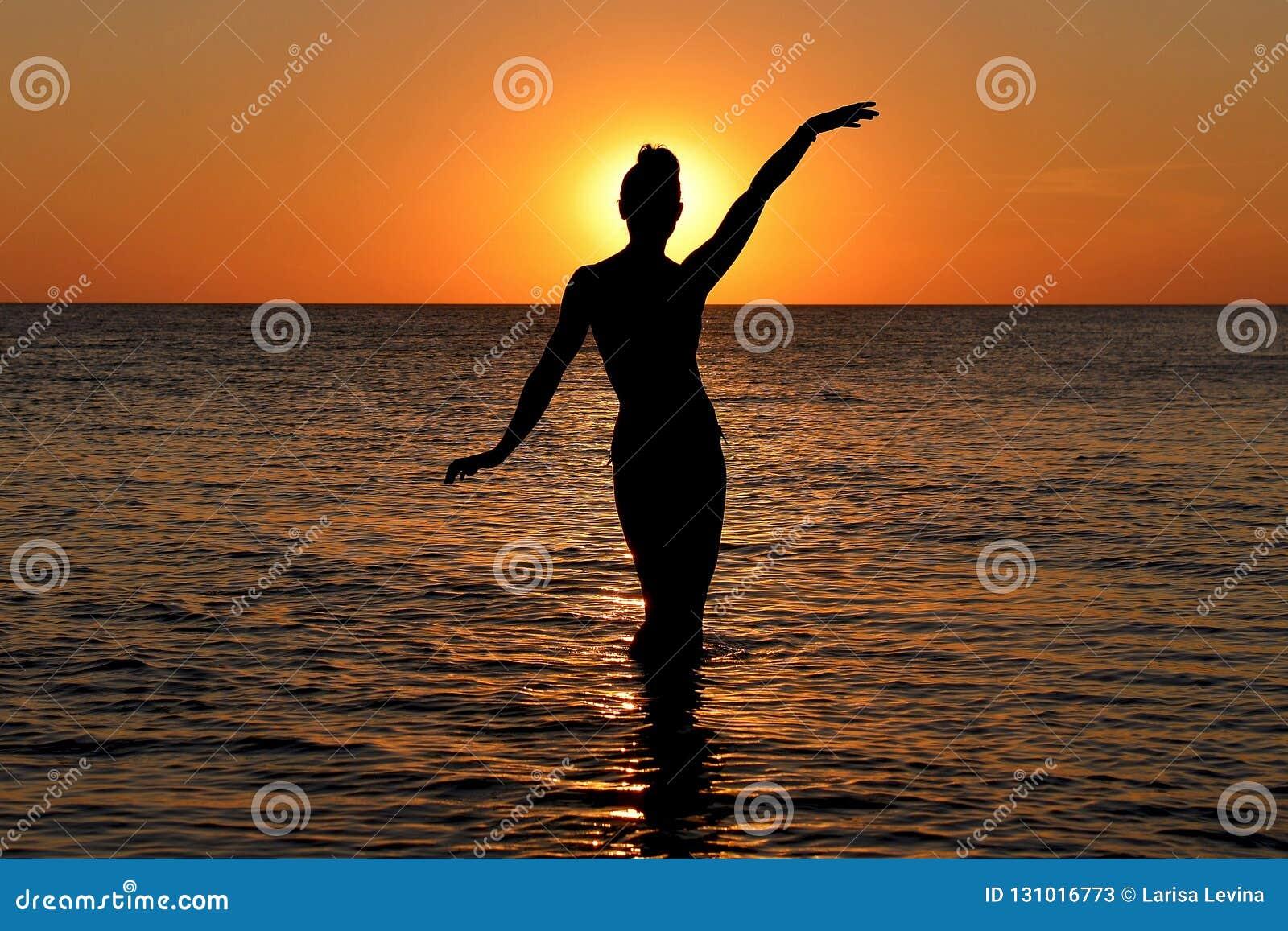 Silueta de una figura femenina misteriosa en el fondo de la puesta del sol del mar