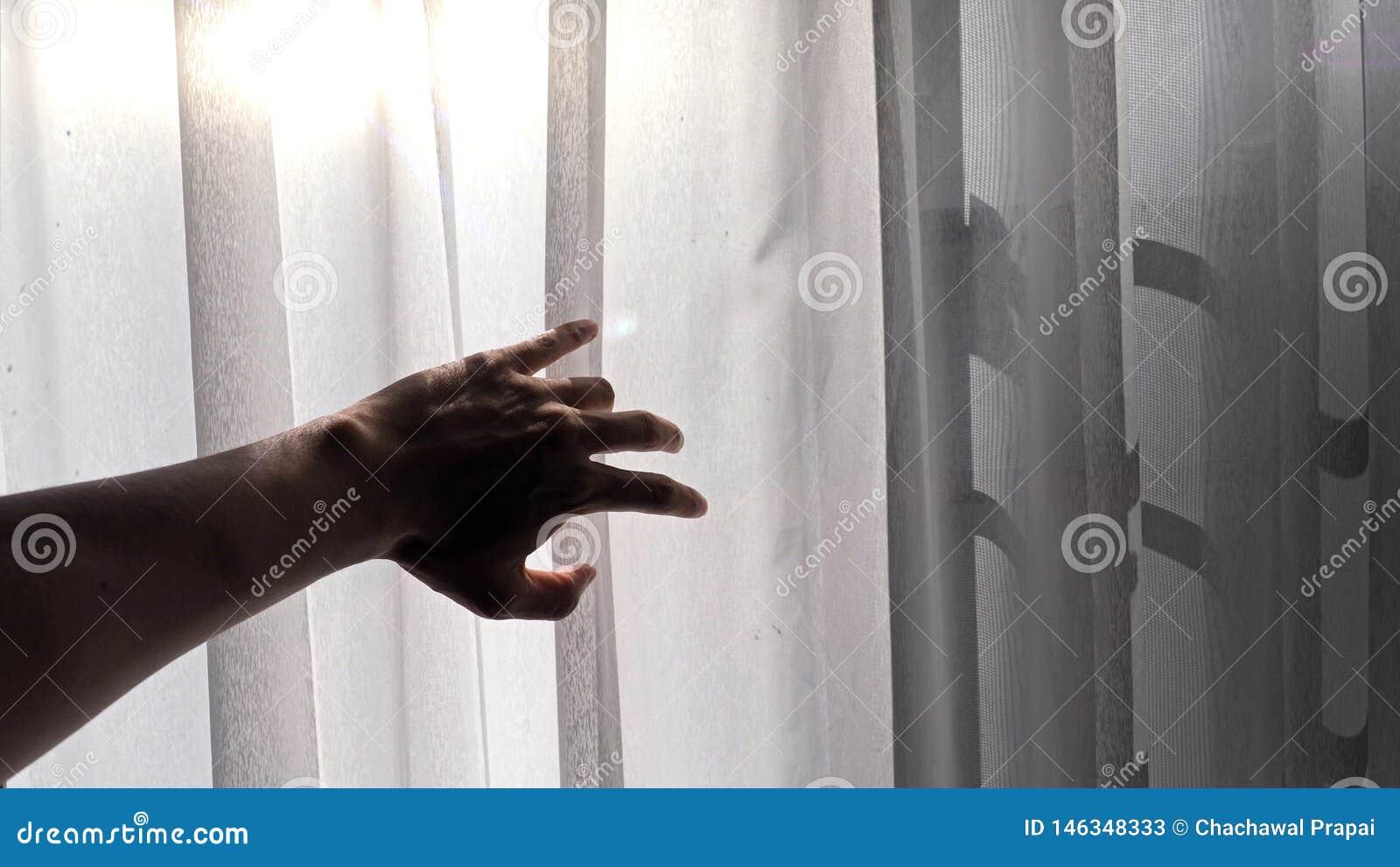 Silueta de una mano masculina que alcanza hacia fuera a la cortina blanca con efecto de la luz del sol de la ma?ana