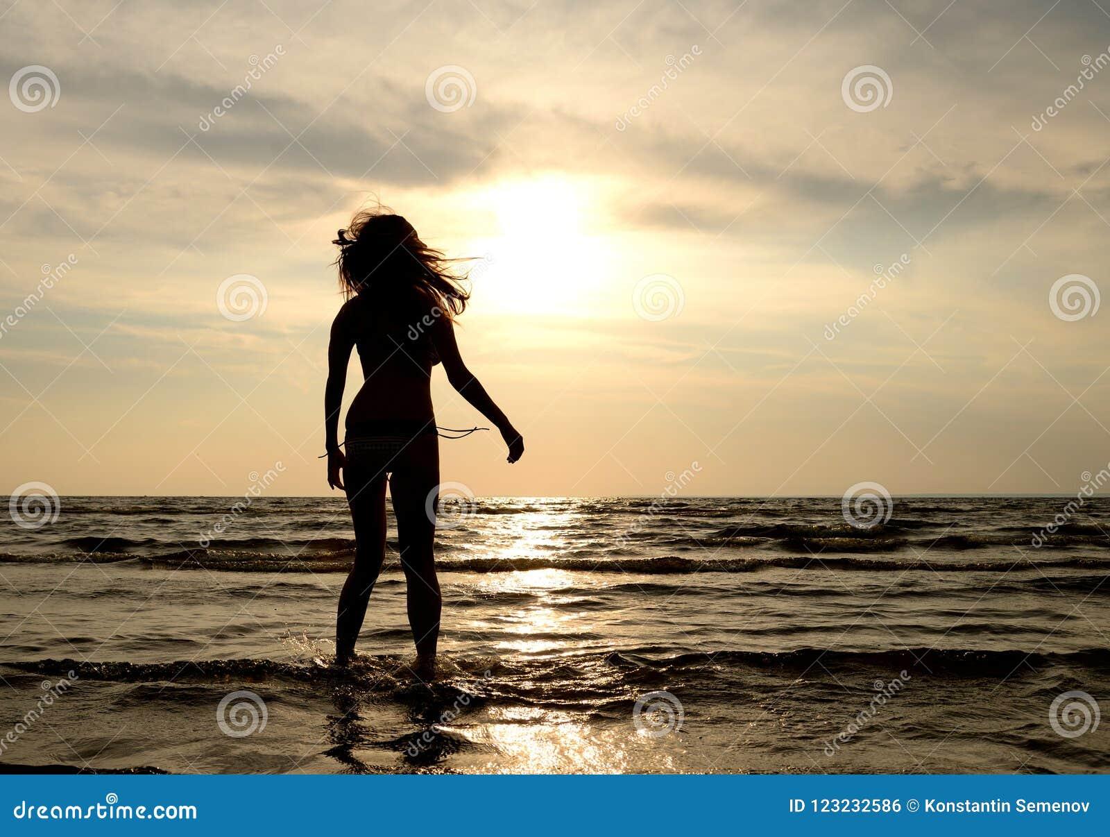 Silueta De Una Mujer Joven En El Mar En La Puesta Del Sol