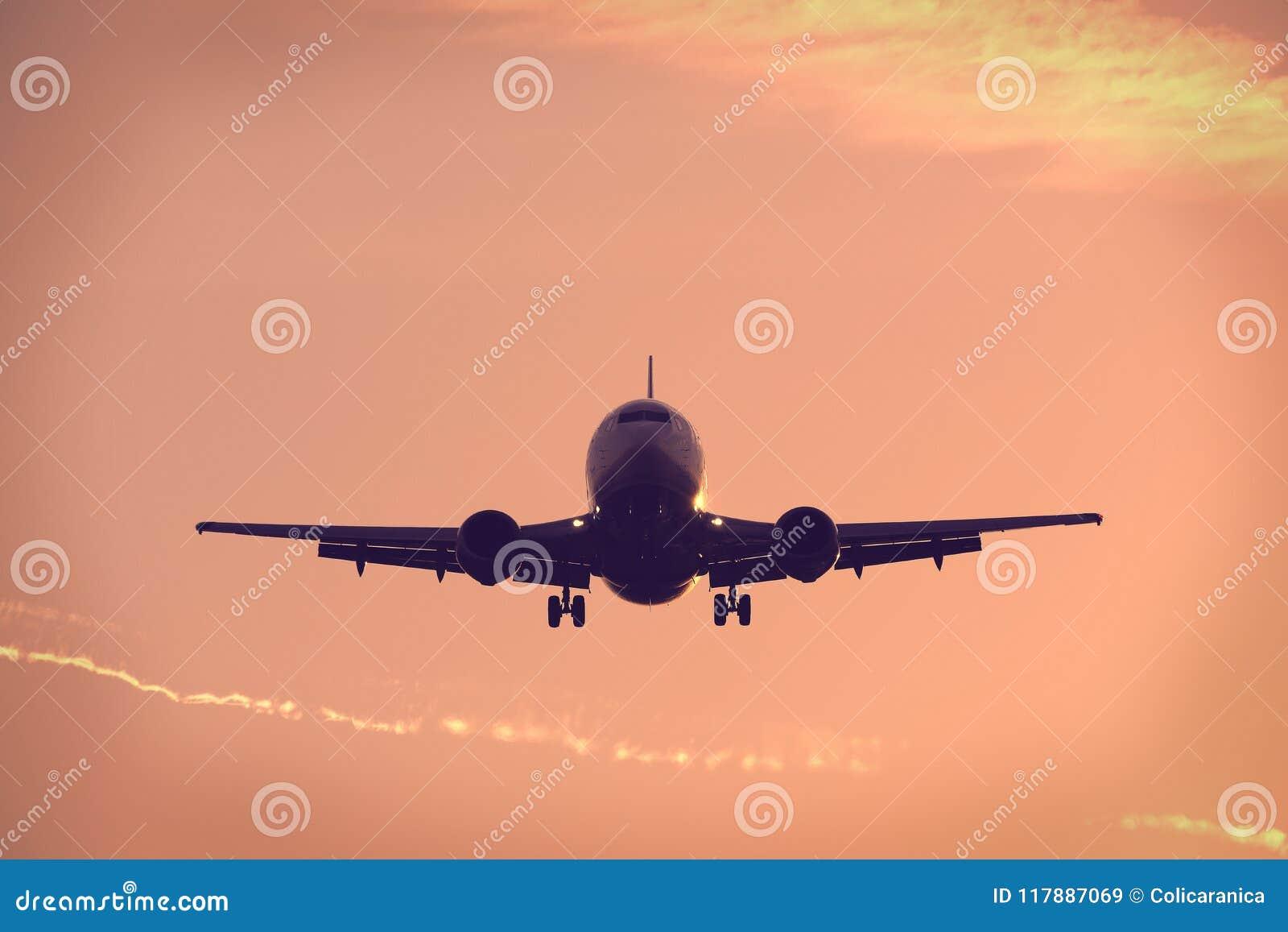 Silueta de volar plano para arriba en el cielo azul, aterrizando