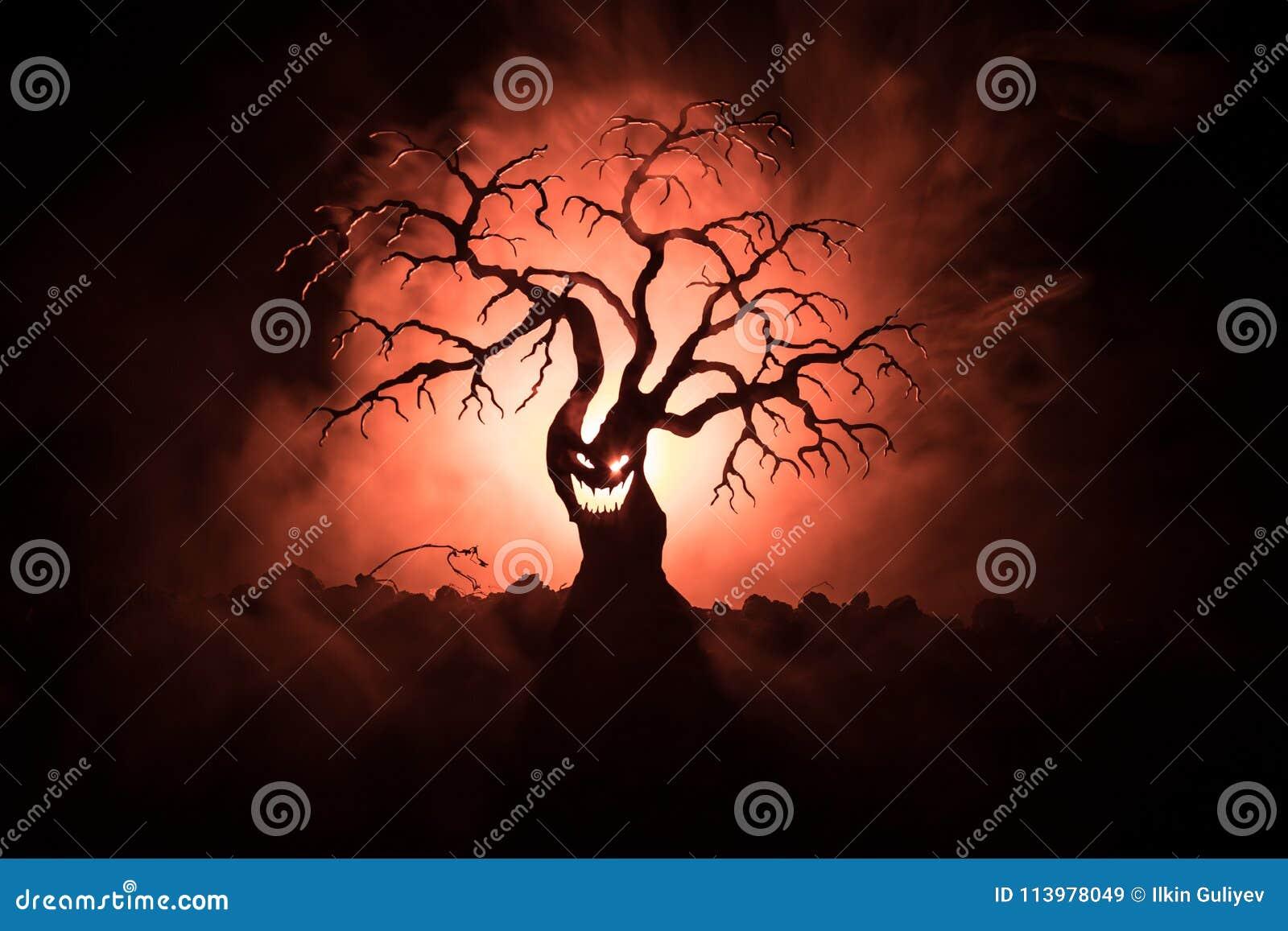 Silueta del árbol asustadizo de Halloween con la cara del horror en fondo entonado de niebla oscuro con la luna en lado trasero Á