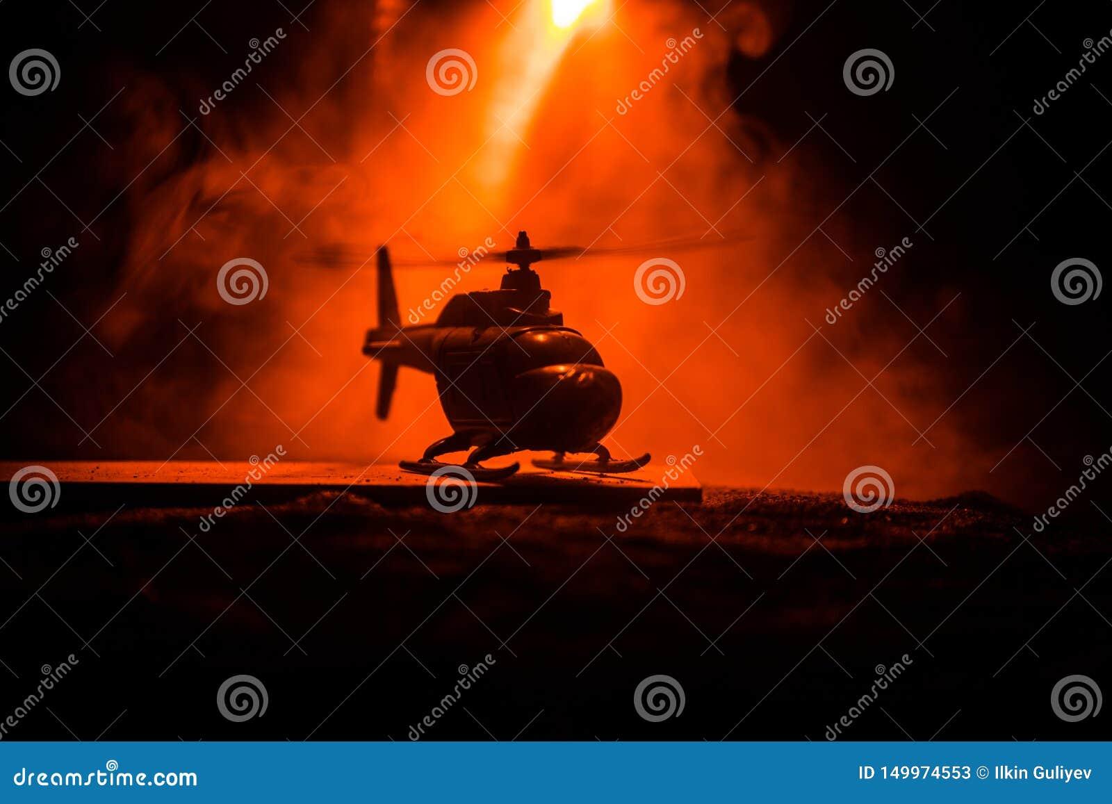 Silueta del helic?ptero militar lista para volar de zona del conflicto Cantidad adornada de la noche con el helic?ptero que comie