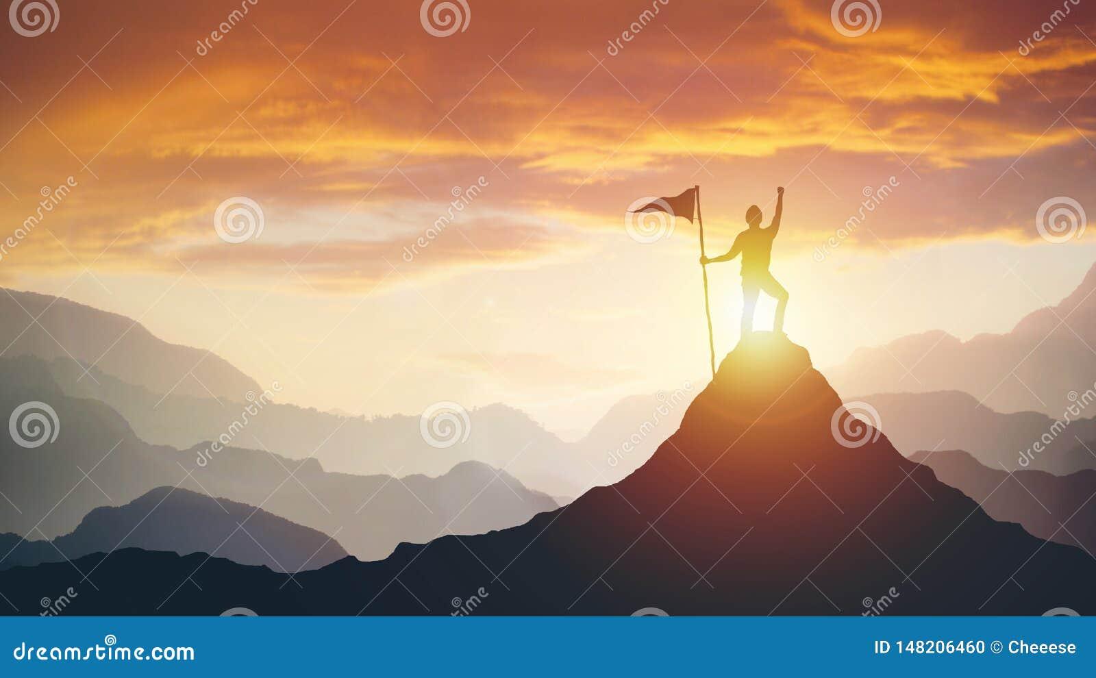 Silueta del hombre de negocios con la bandera en el top de la montaña sobre fondo de la luz del cielo y del sol