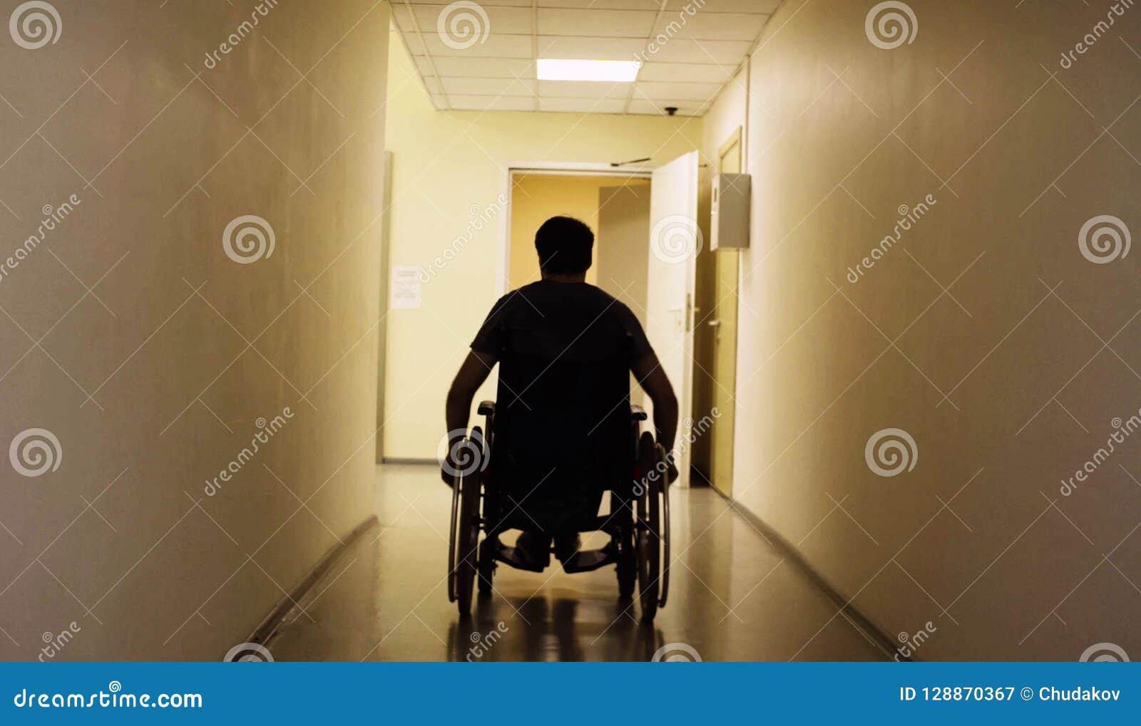 Silueta del hombre discapacitado en una silla de ruedas en el centro de rehabilitación