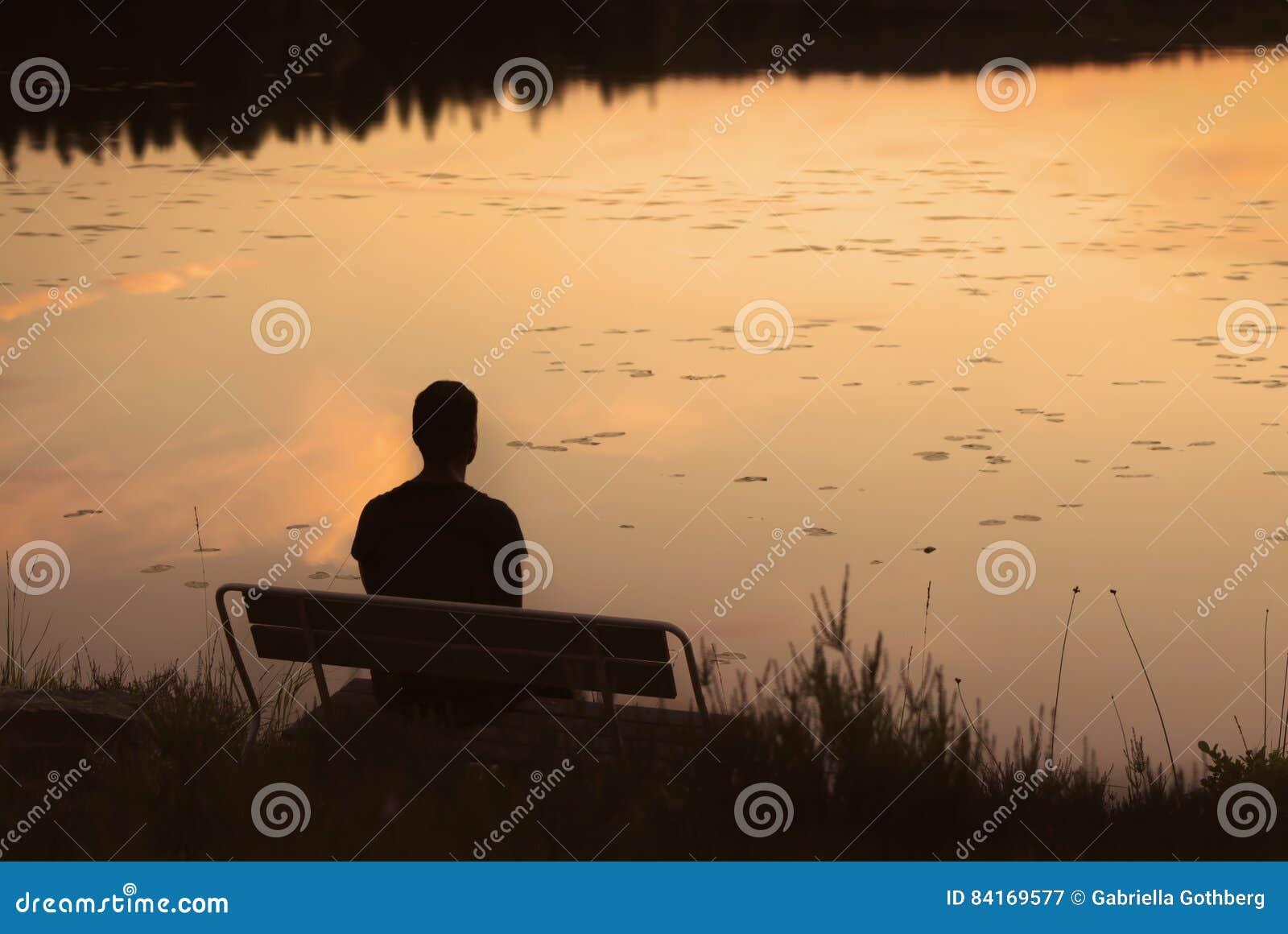 Silueta del hombre en banco en puesta del sol de oro por el lago