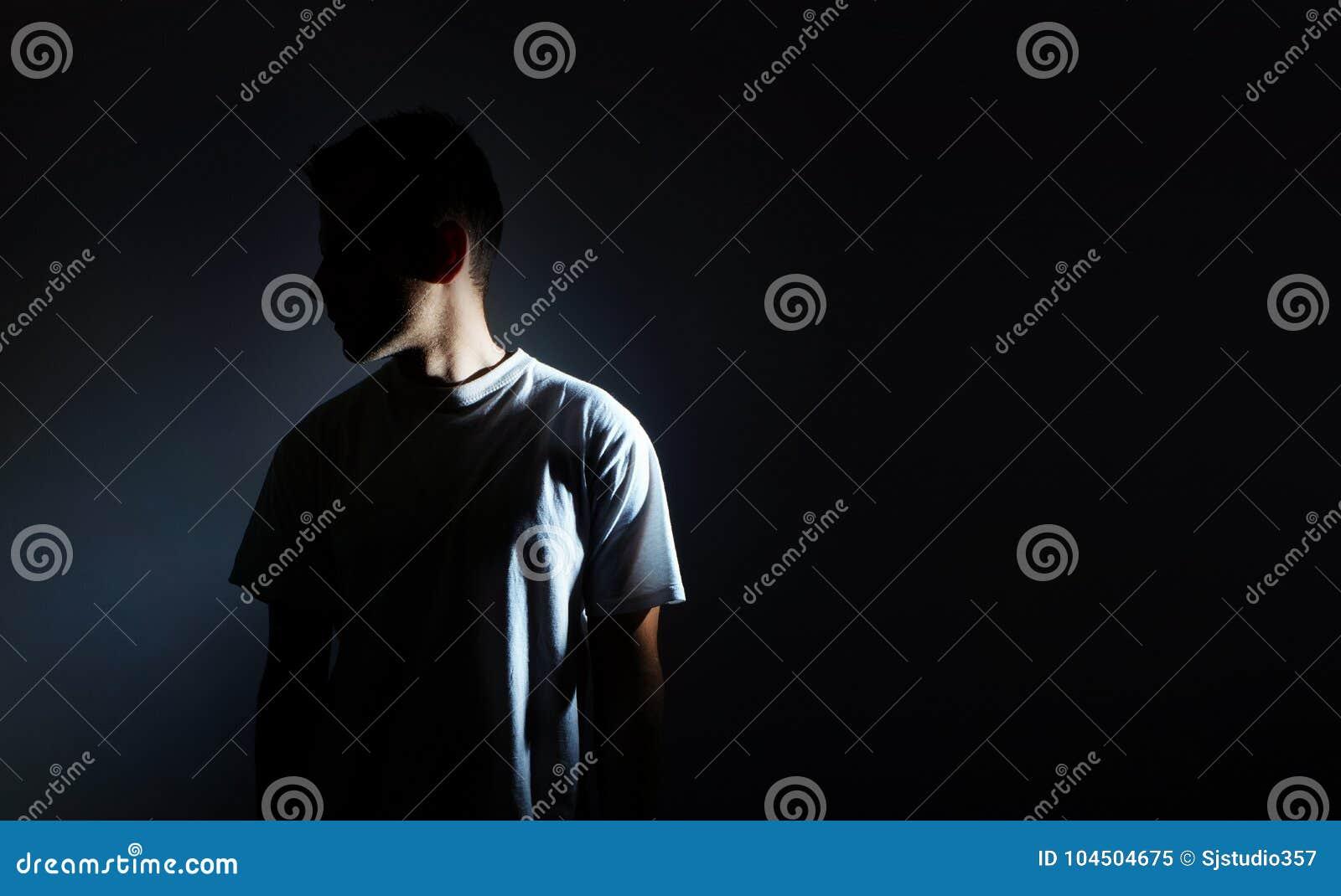 Silueta del hombre en el fondo negro, retrato oscuro, perfil, depresión masculina