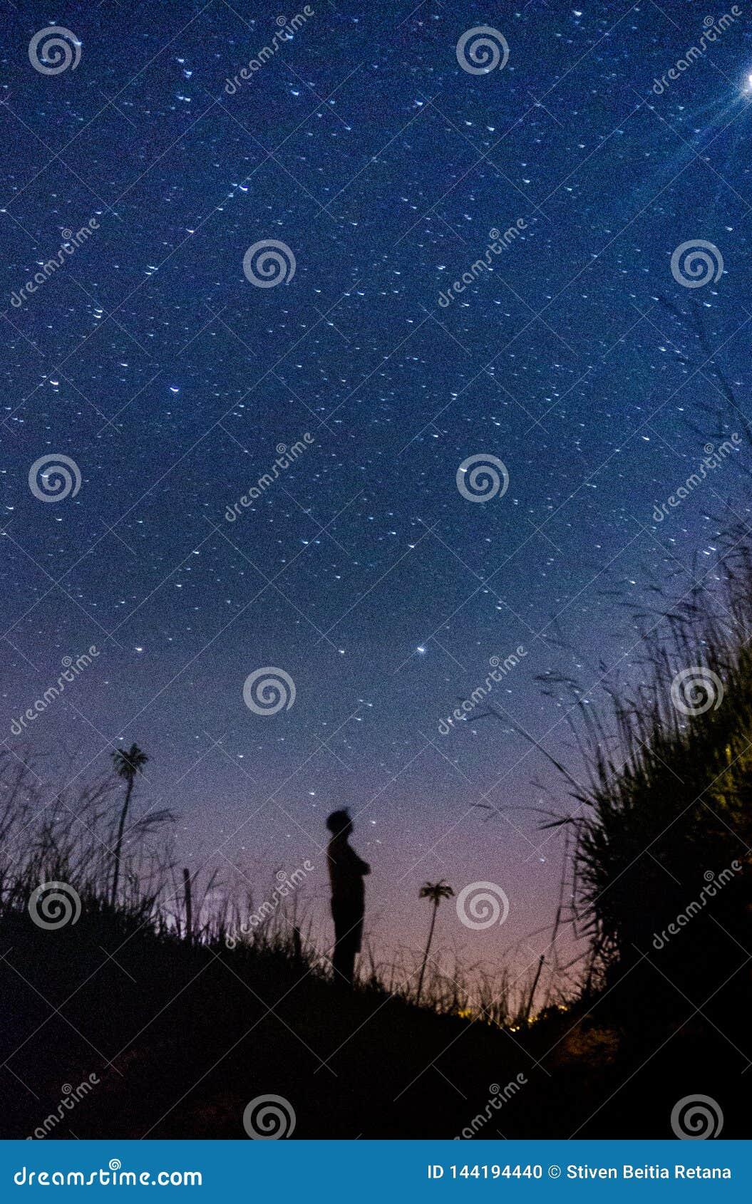 Silueta del hombre que mira el infinito de estrellas