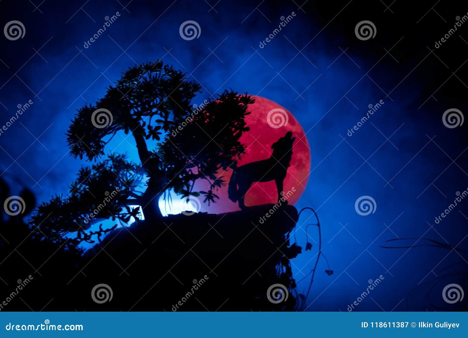 Silueta del lobo del grito contra fondo de niebla entonado oscuro y Luna Llena o lobo en silueta que gritan a la Luna Llena hola