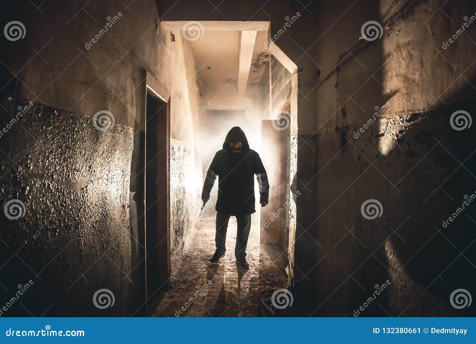 Silueta del maniaco del hombre o del asesino o del asesino del horror con el cuchillo a disposición en pasillo espeluznante y fan