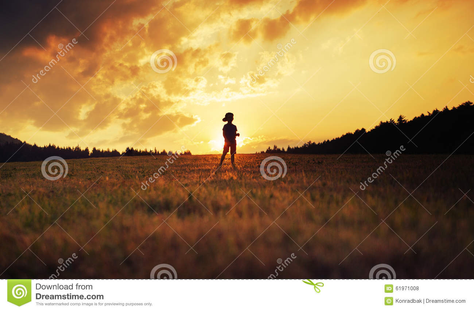 Silueta del niño feliz que juega en prado en la puesta del sol
