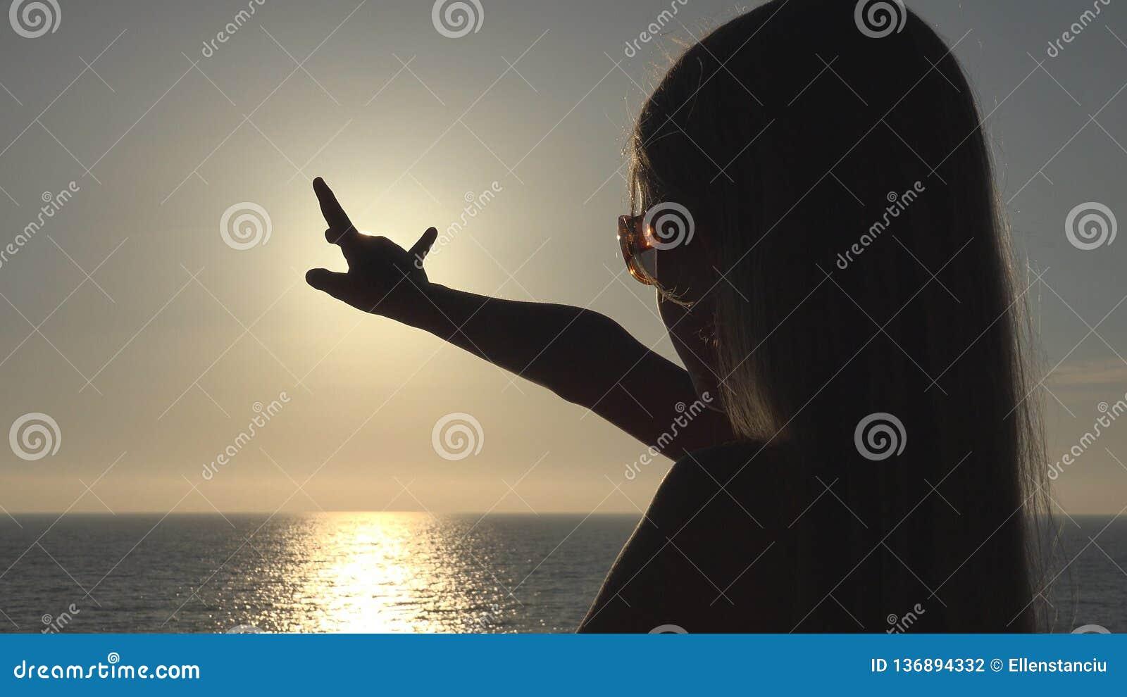 Silueta del niño que juega en la playa, niño en la puesta del sol, mano en los rayos de Sun, haz de la muchacha