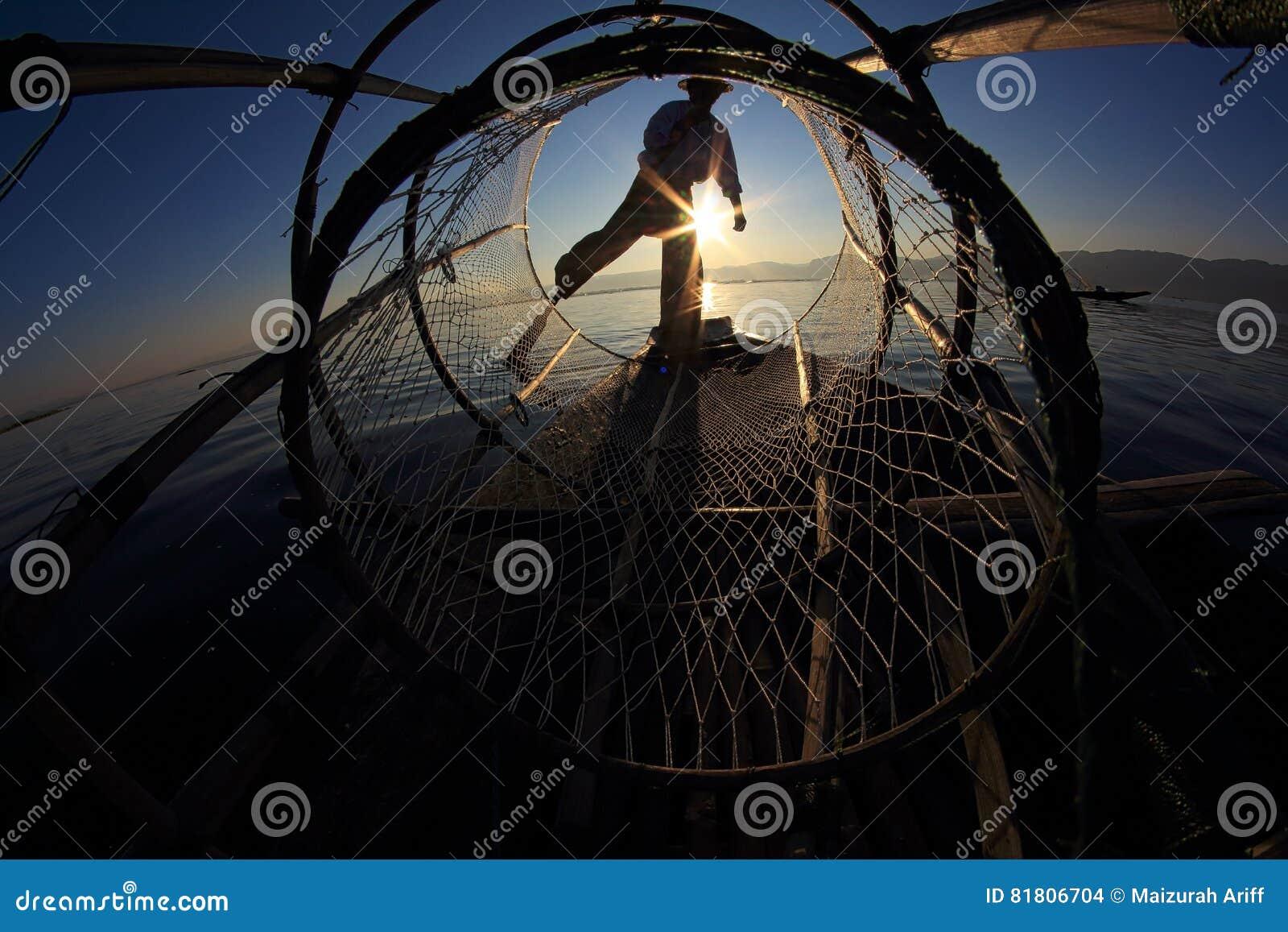 Silueta del pescador del intha contra el cielo de la puesta del sol