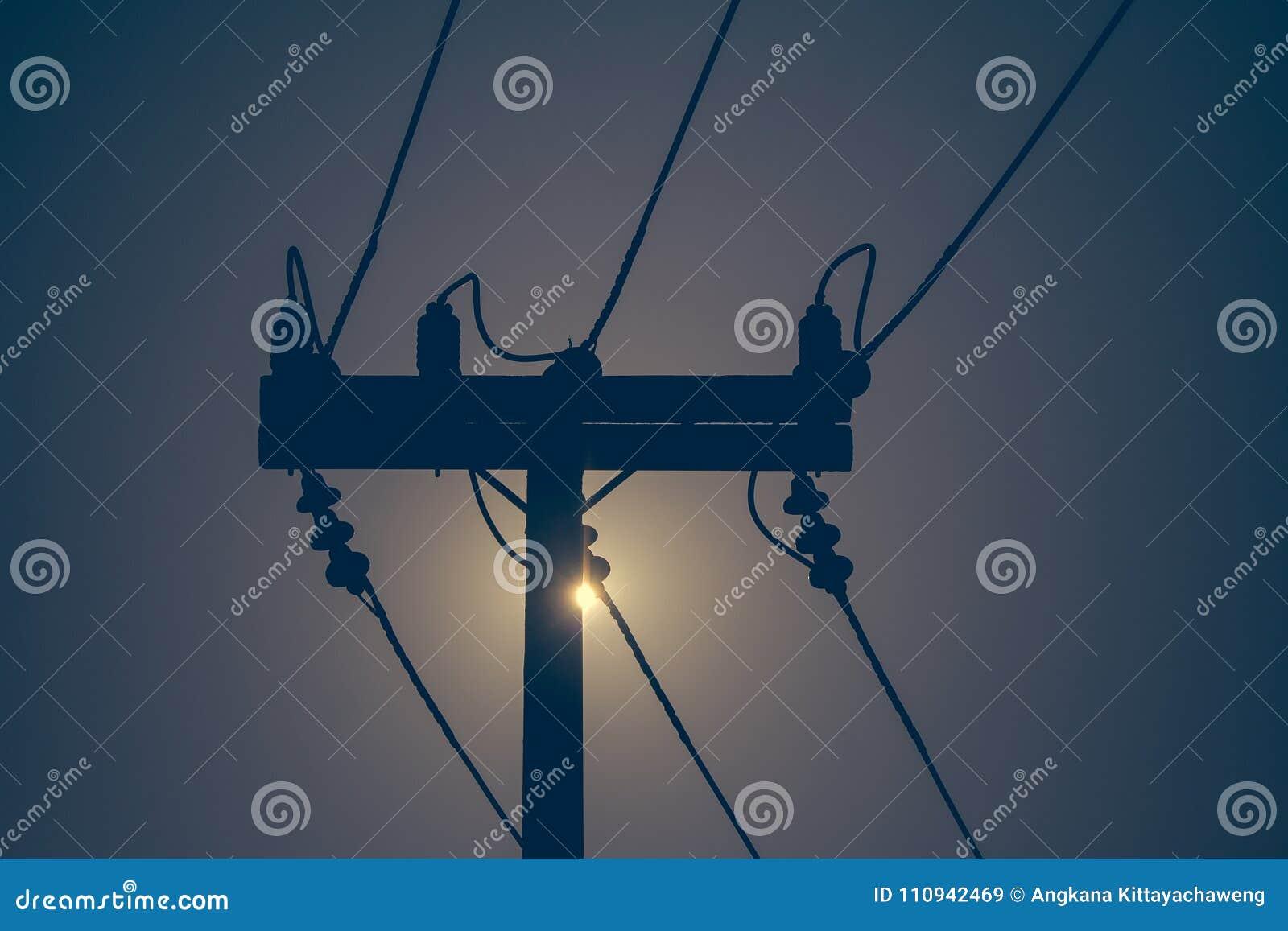 Silueta del polo de la electricidad y de la línea eléctrica del alto voltaje con puesta del sol en el fondo