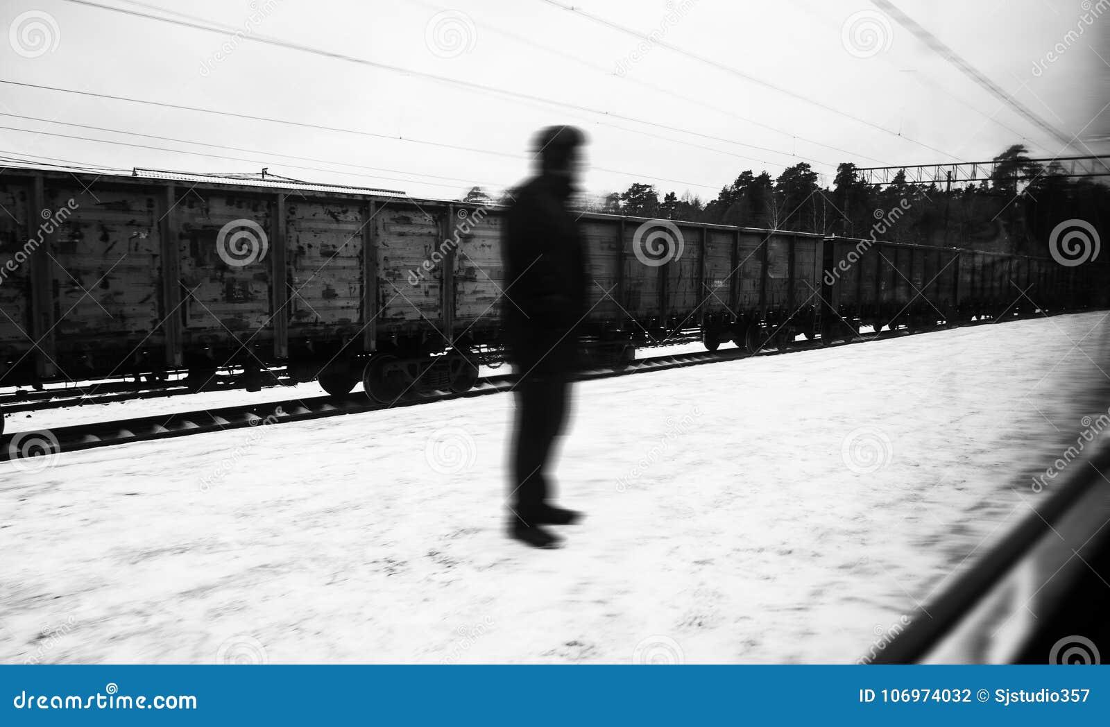 Silueta desconocida de la persona de un hombre místico extraño, colocándose en la calle, en el fondo de los carros del tren de ca