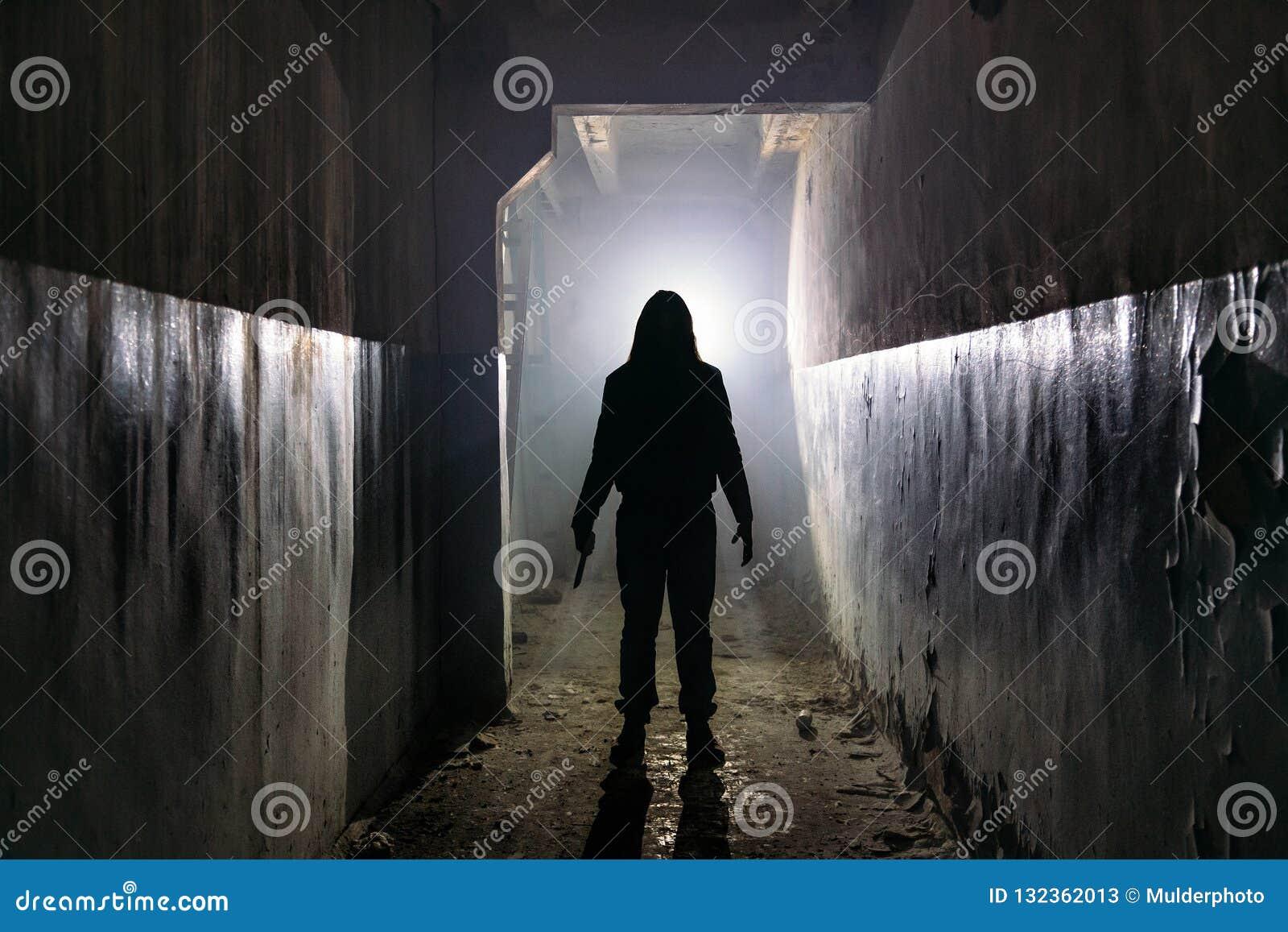 Silueta espeluznante del hombre desconocido con el cuchillo en el edificio abandonado oscuro Horror sobre concepto maniaco