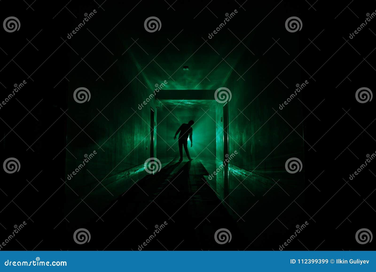 Silueta espeluznante en el edificio abandonado oscuridad Pasillo oscuro con las puertas de gabinete y luces con la silueta del ho