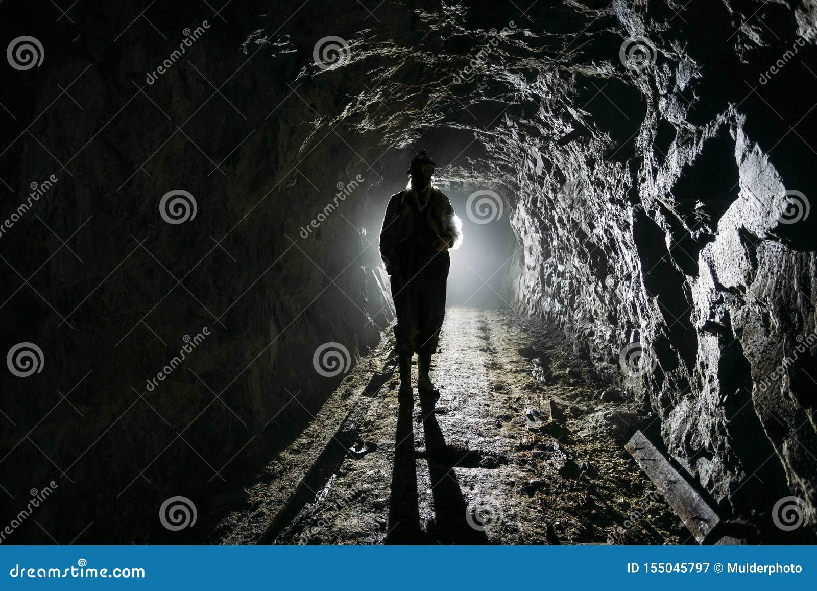 Silueta humana retroiluminada espeluznante dentro de la mina abandonada oscura