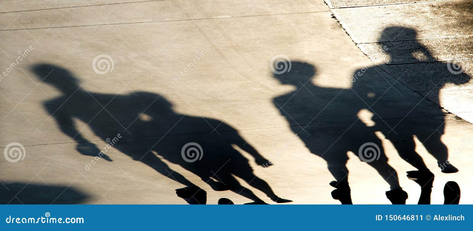 Siluetas borrosas de las sombras de la gente joven que camina en puesta del sol del verano