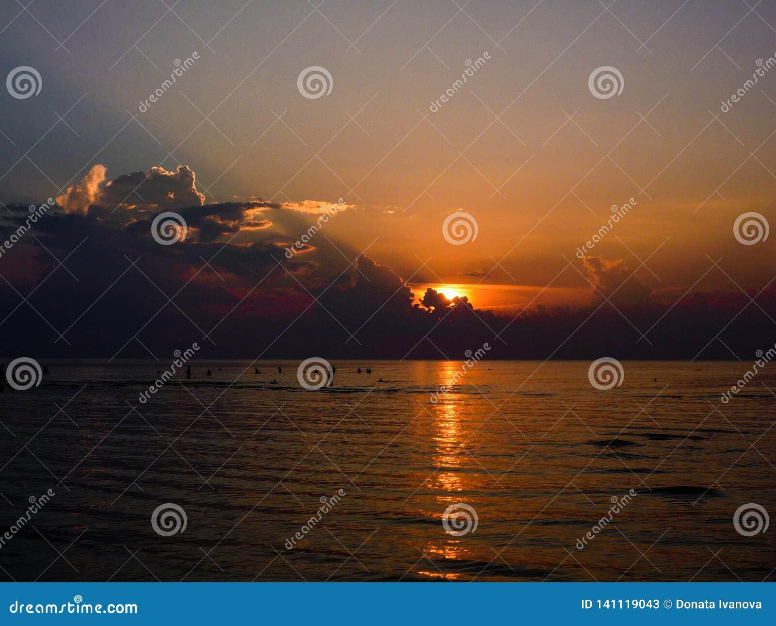 Siluetas de la gente bathering en el mar en un backgroun de la puesta del sol