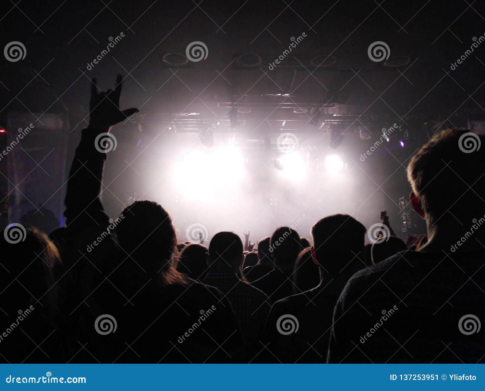 Siluetas de la gente en un concierto Concierto del estallido Grupo de rock El individuo hace una cabra por las manos Luz brillant