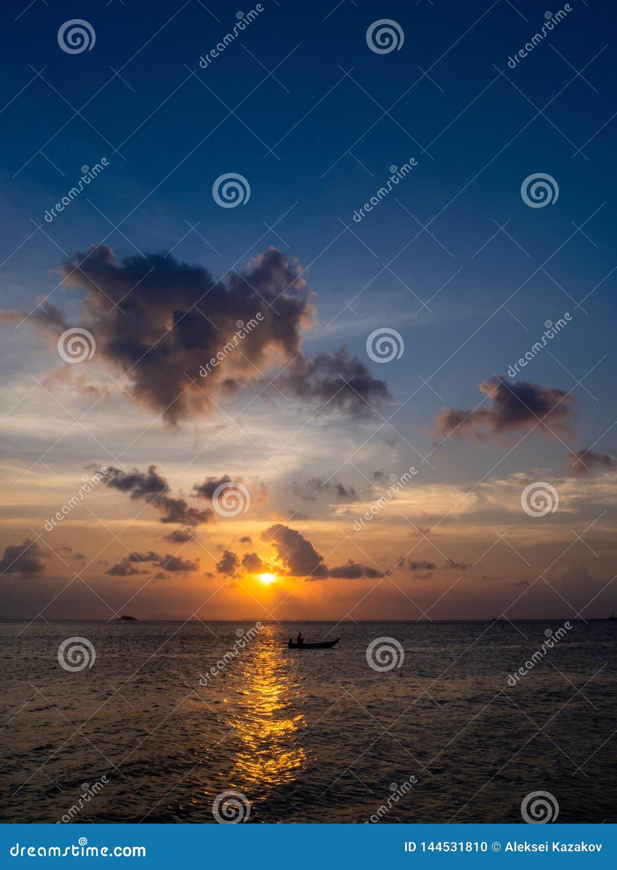 Siluetas de la gente en un kajak en los rayos del sol poniente contra la perspectiva de las nubes